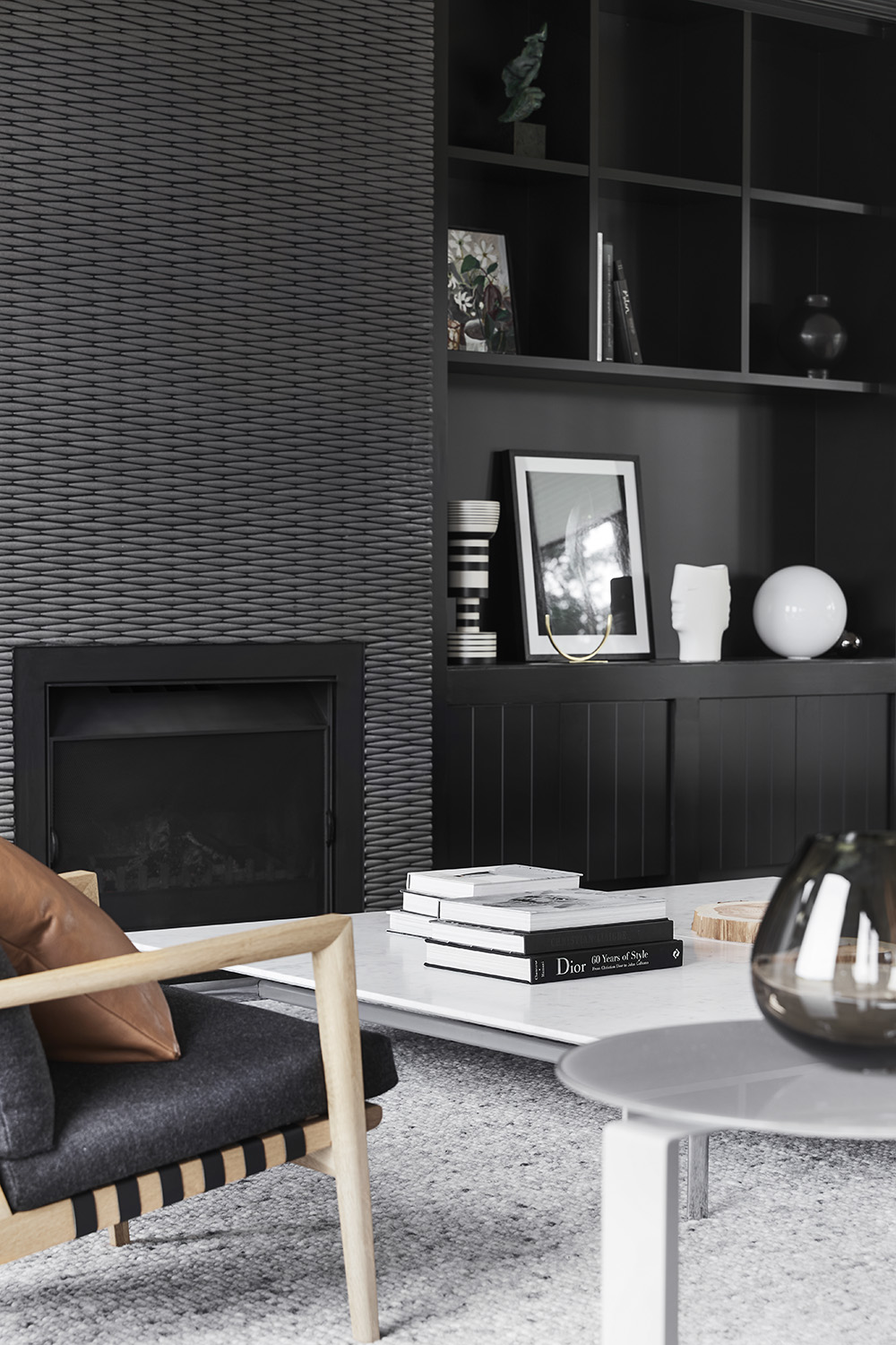 Modern black shelving and cabinetry can be found on either side of a focal fireplace with a silvery-grey tiled surround.