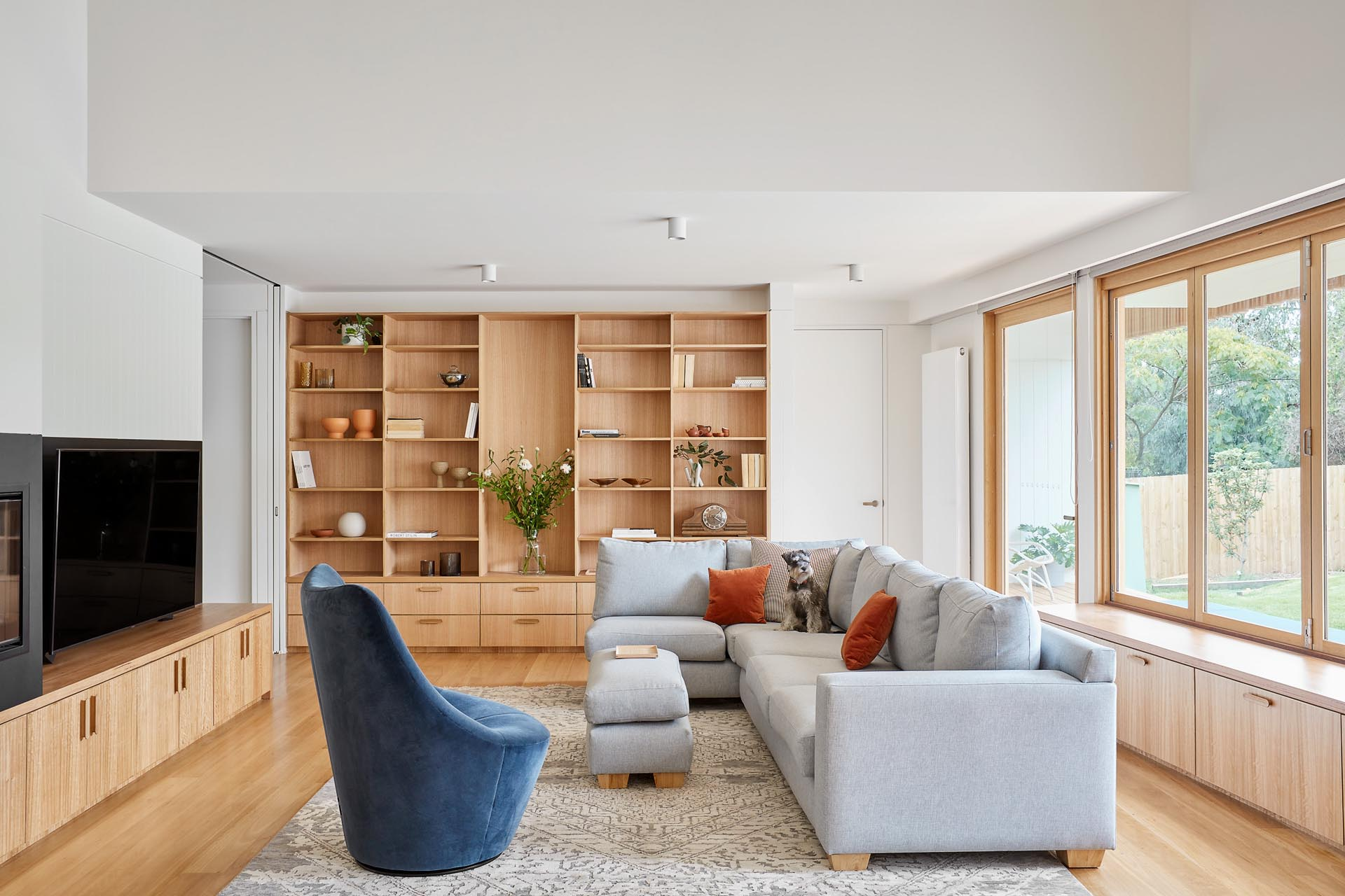 A modern living room with a custom designed wood shelving unit that includes drawers underneath.