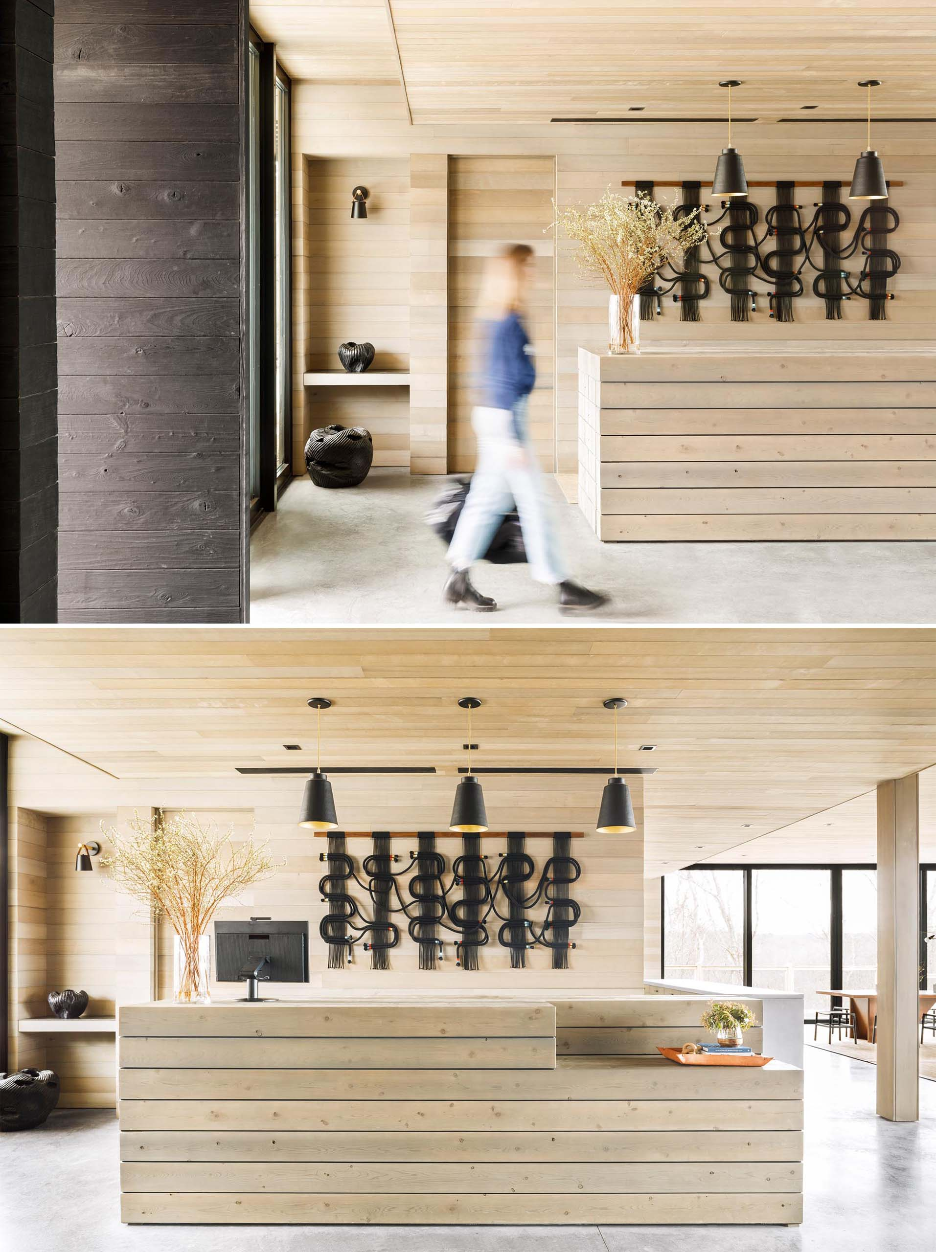 A modern lobby with a wood welcome desk that matches the wood walls and ceiling.
