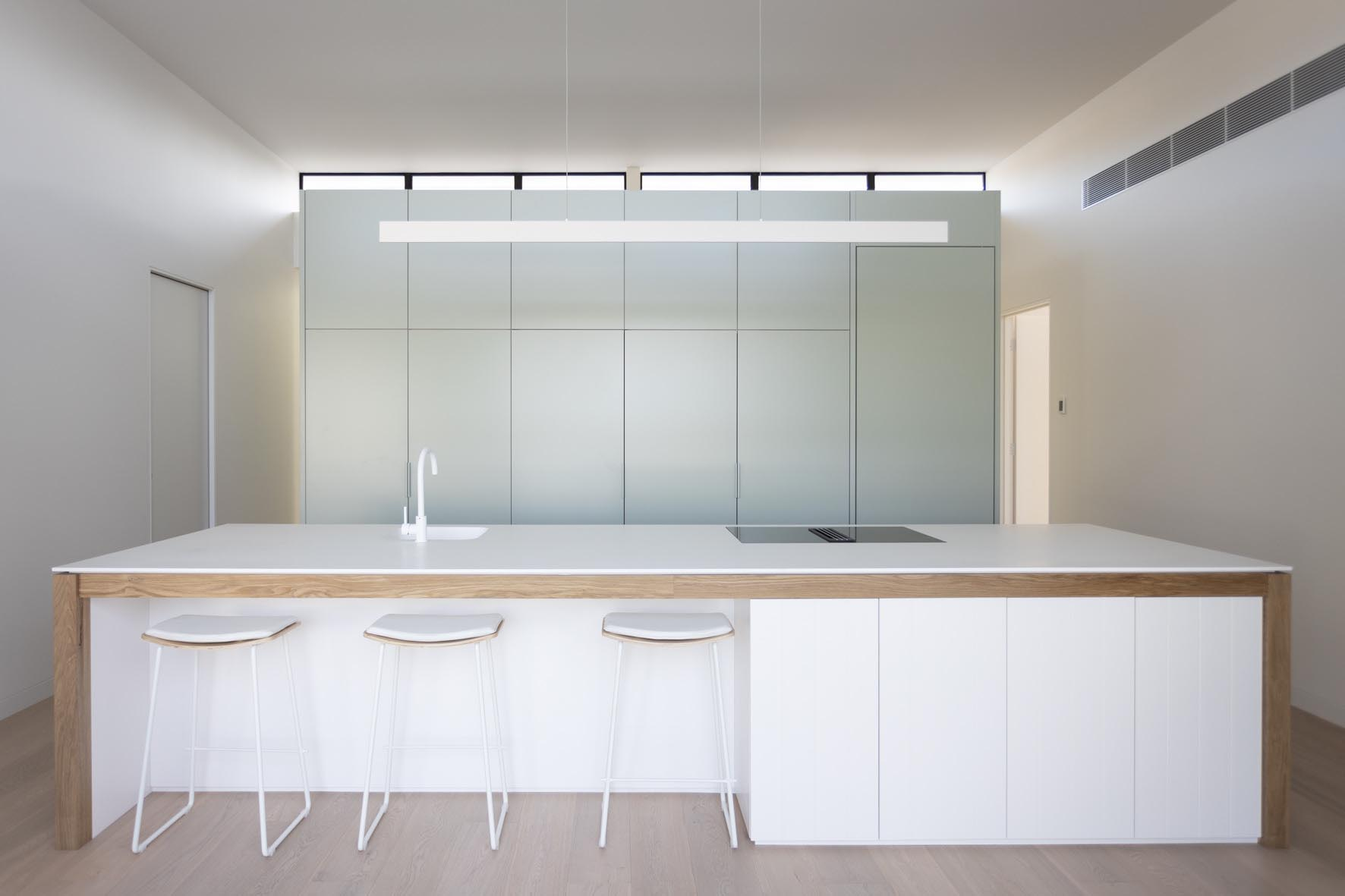 This kitchen has a minimalist design that includes an integrated fridge, and a large white island with wood detailing.