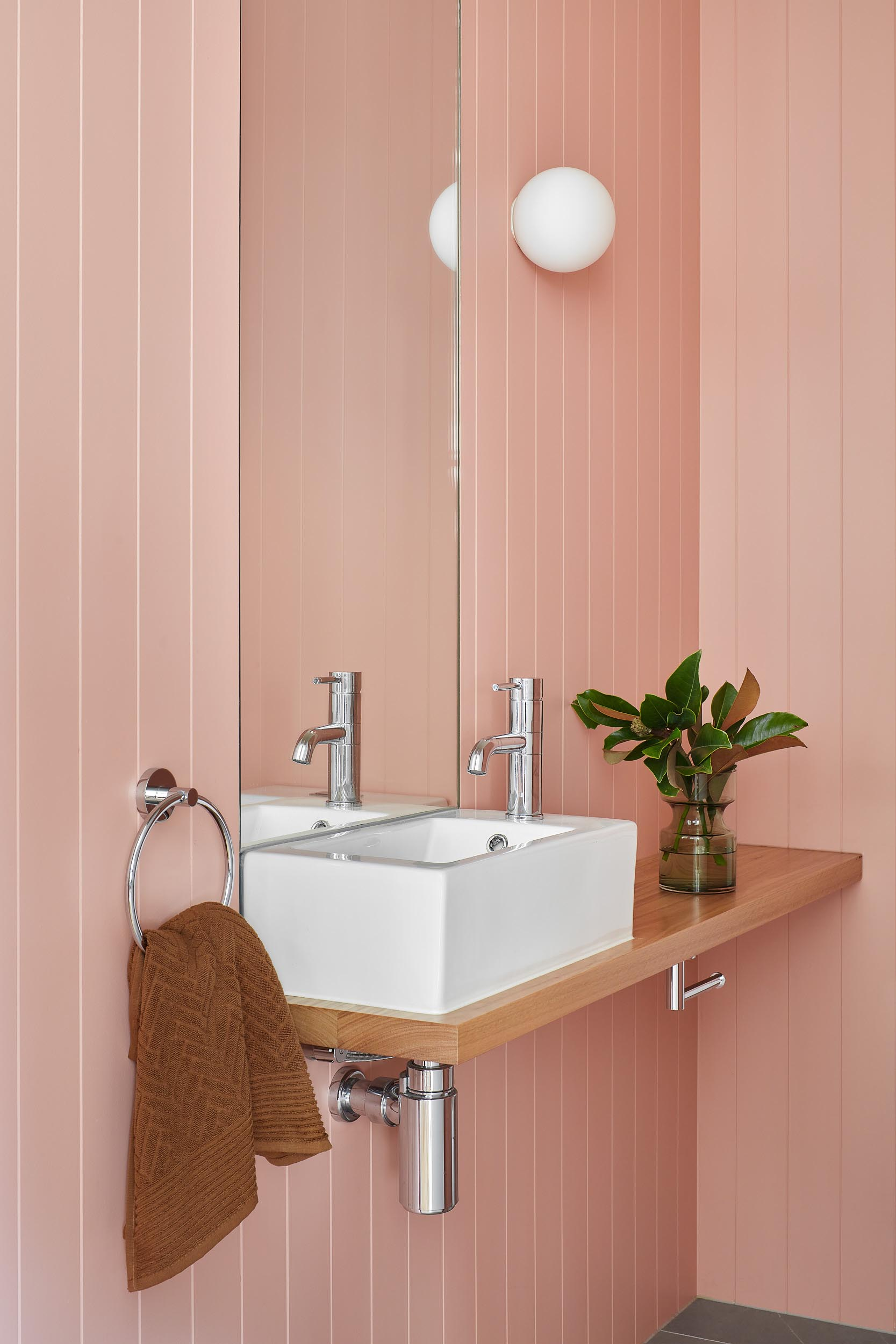 Soft pink walls add a colorful touch to this modern bathroom.