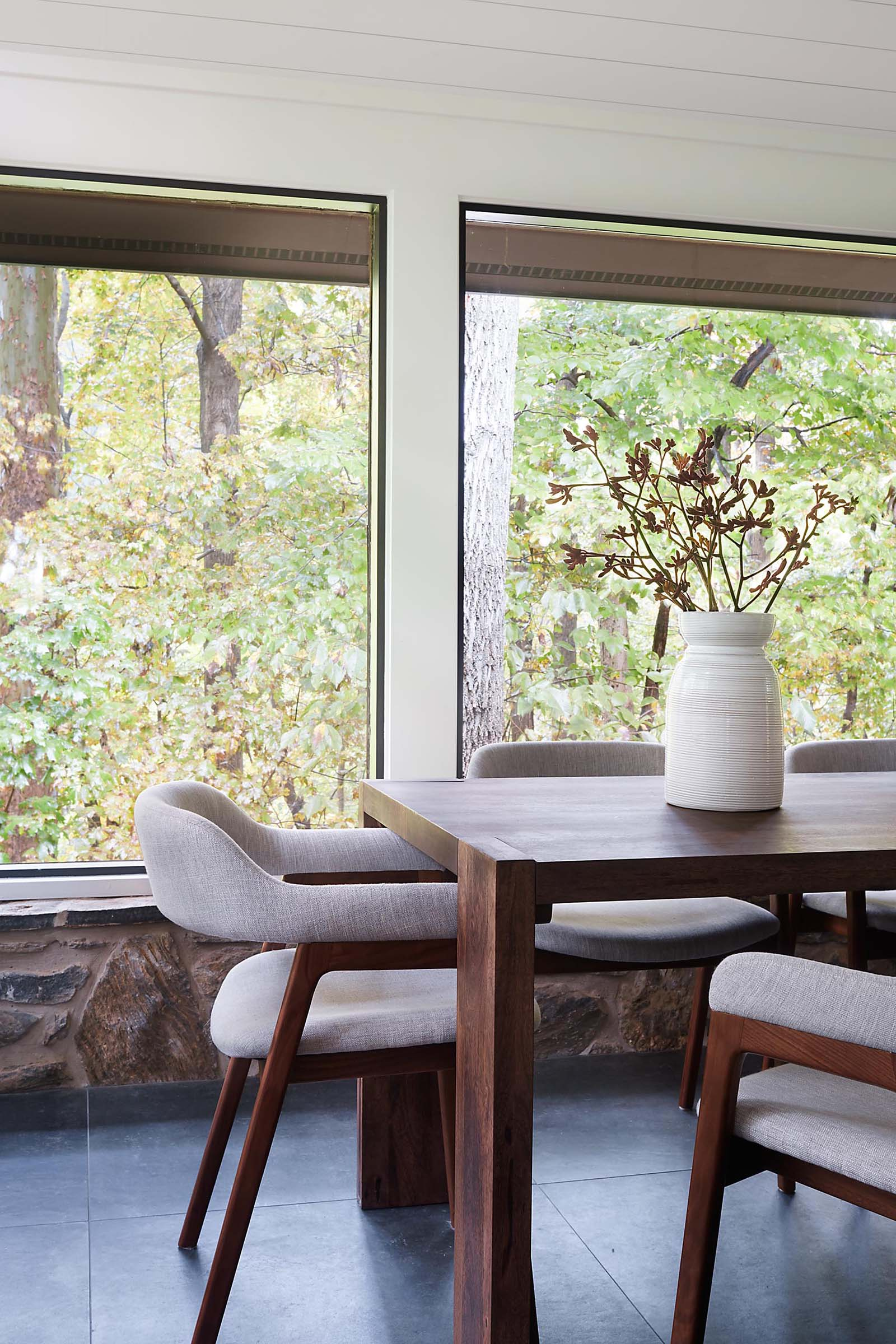 A modern dining room surrounded by windows has large format floor tiles.