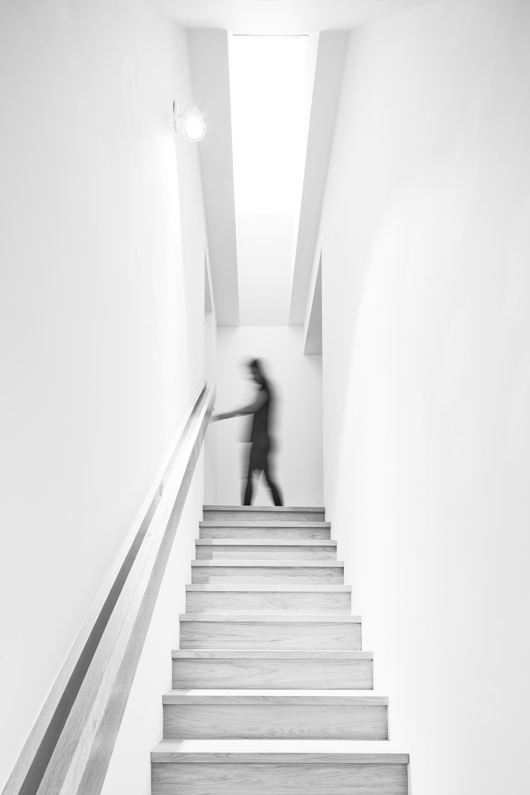 A staircase surrounded by white walls connects the social areas with the bedrooms and bathrooms on the upper floors of the home.