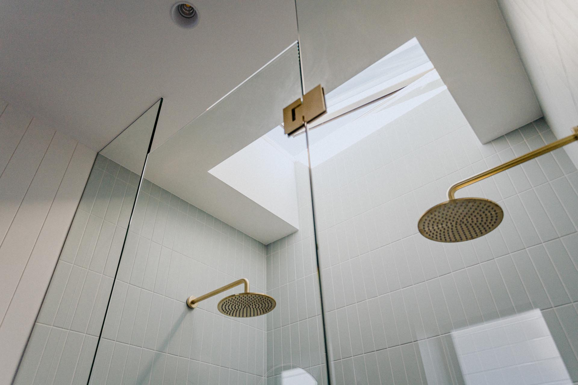 In this modern shower, there's dual shower heads, a frameless glass door, white tiles, and a skylight.