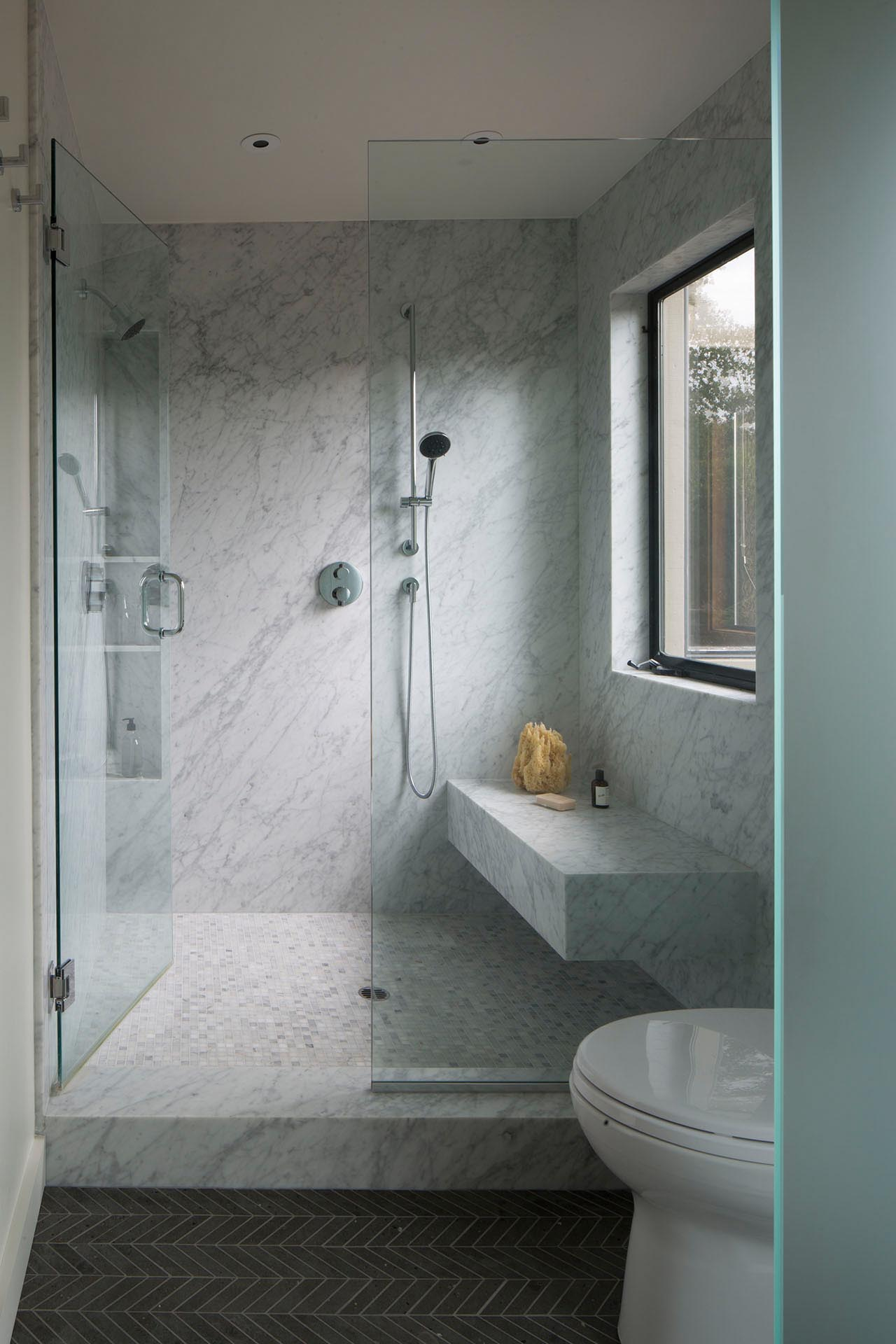 A modern bathroom with a walk-in shower that includes a bench and built-in shower niche.
