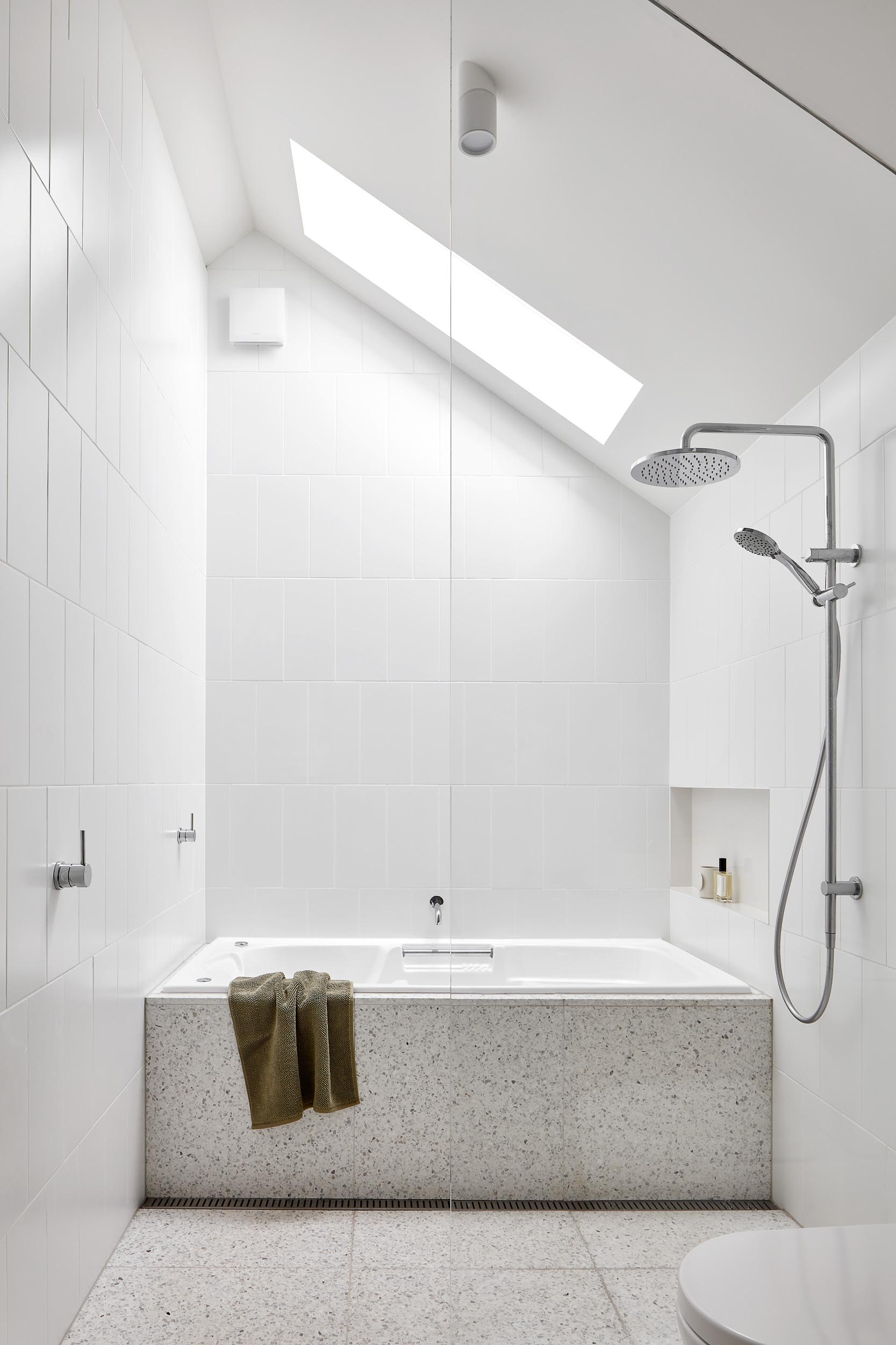 The terrazzo flooring in this bathroom travels through the shower and wraps onto the surround of the built-in bathtub.
