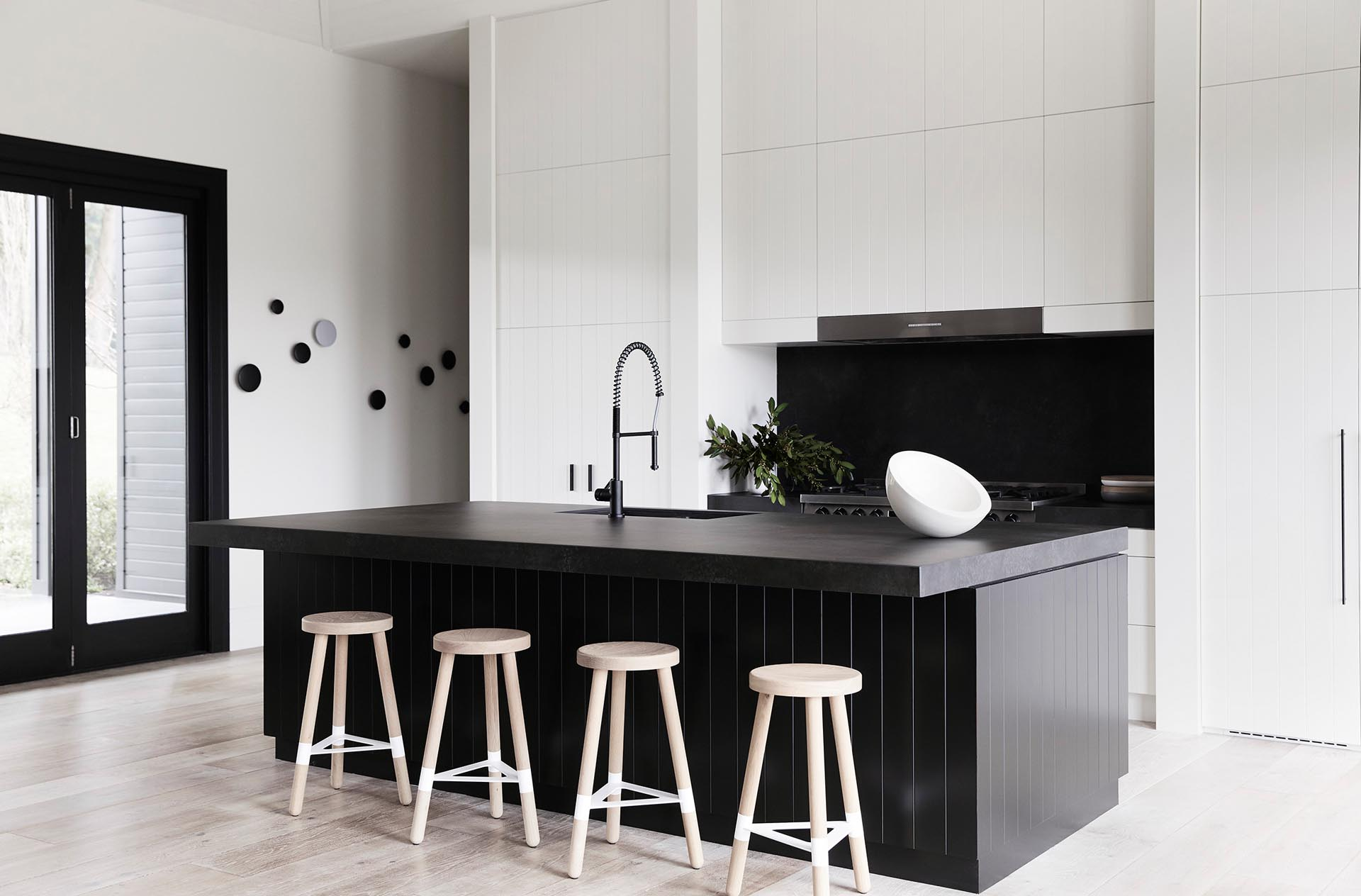 In this modern kitchen, there's minimalist white cabinets with integrated appliances, as well as a large black island that measures in at almost 10 feet (3m), and includes a black stone countertop that overhangs to provide room for seating.