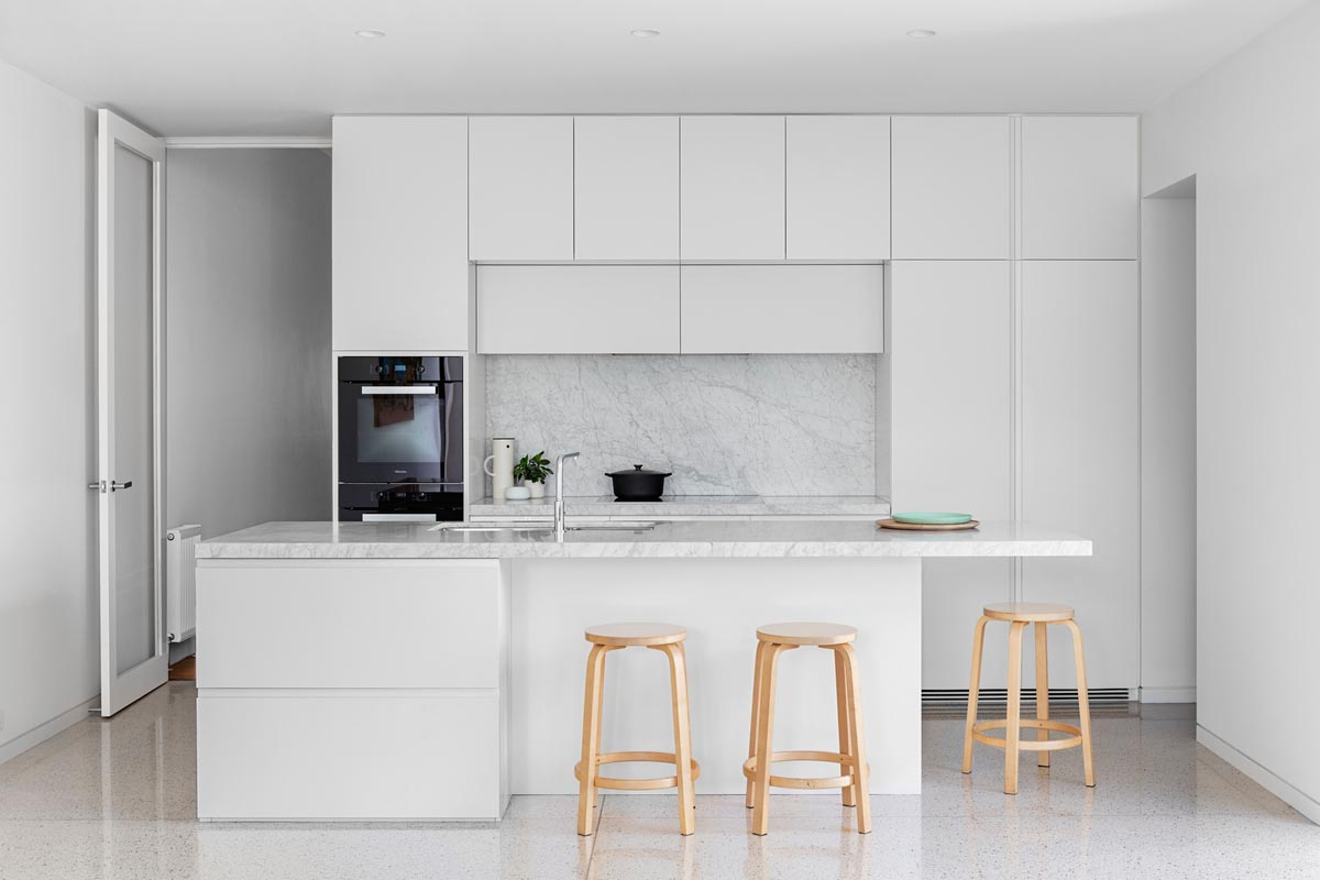 In this all-white kitchen, minimalist hardware free white cabinets have been paired with complementing honed Elba countertops.