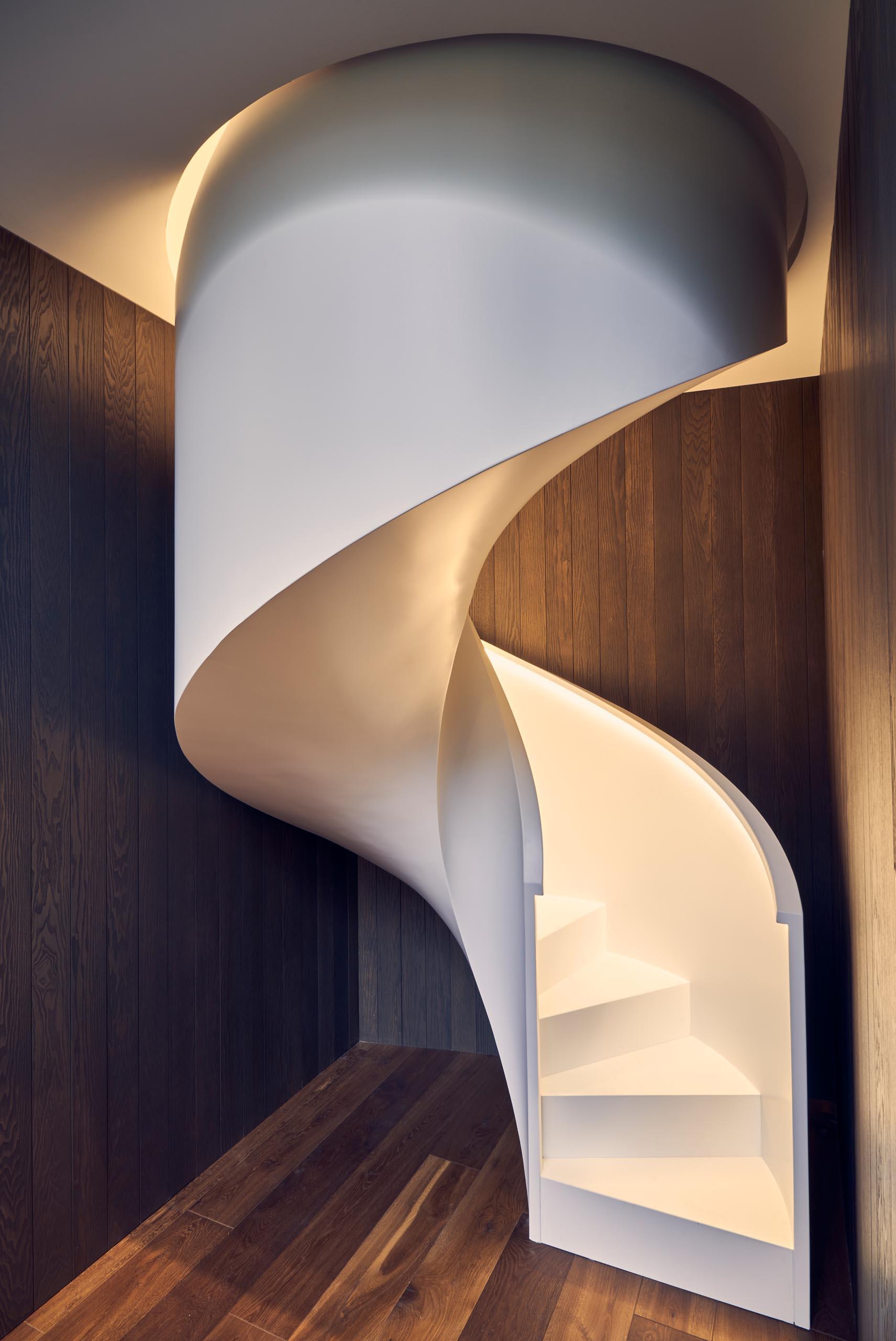 Modern white spiral stairs with hidden lighting.
