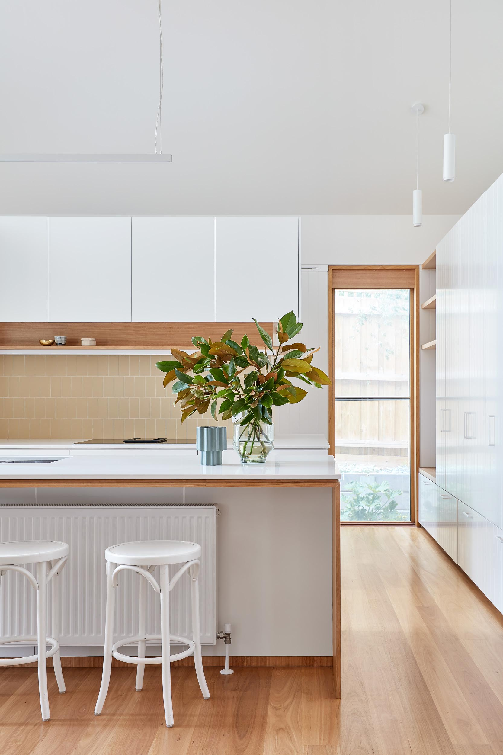 In this modern kitchen, minimalist white cabinets are complemented by the Glacier White Corian countertops and Blackbutt Timber accents.