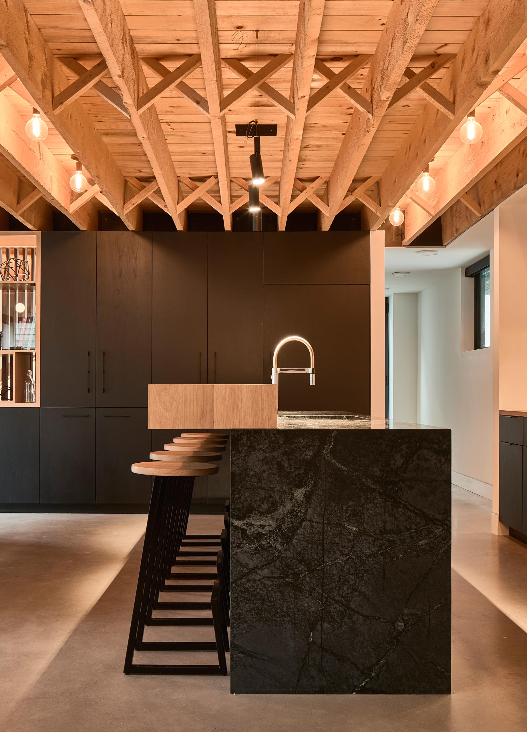 A modern kitchen with custom woodwork, black and wood countertops and black cabinets.