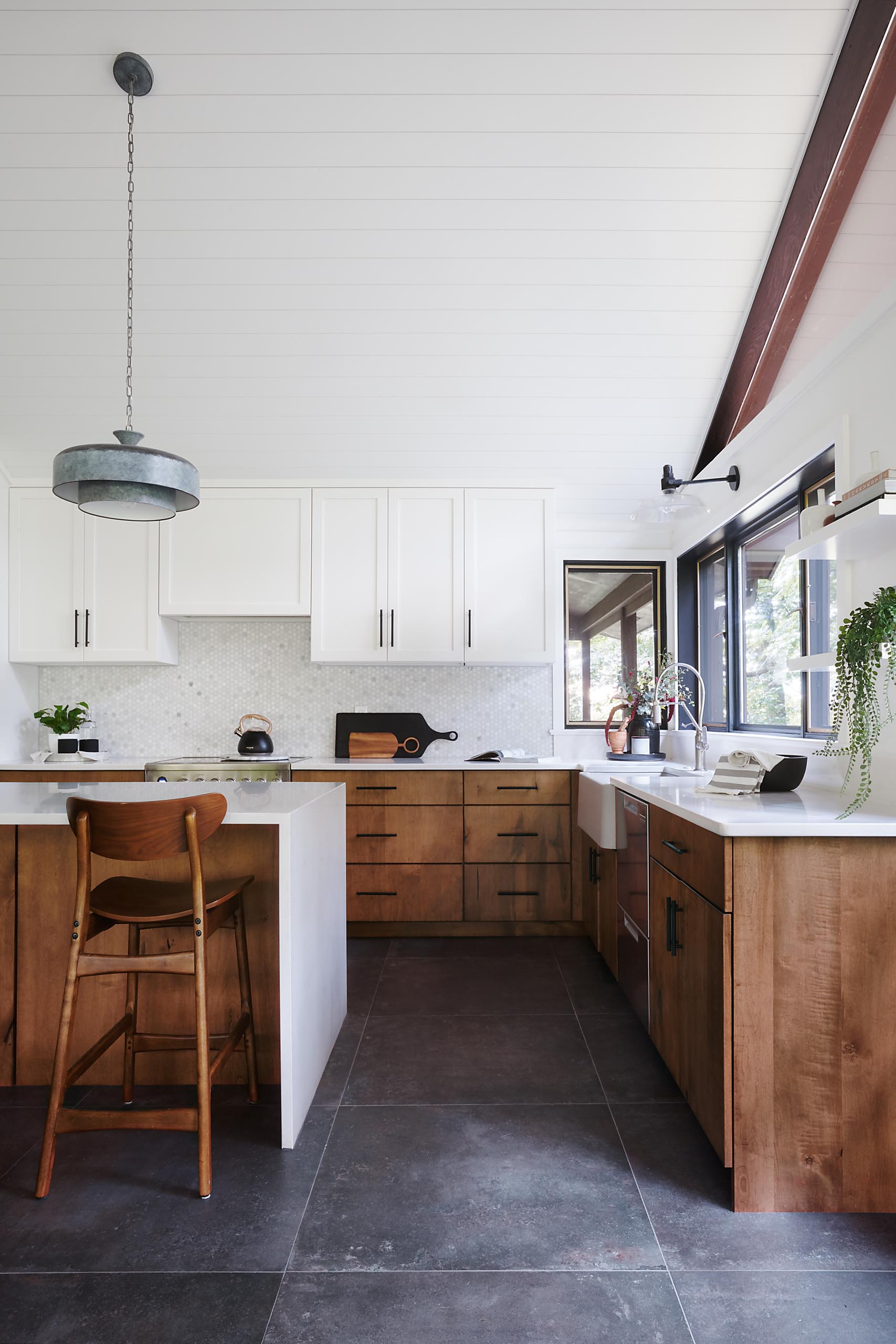 A modern kitchen with white countertops, wood and white cabinets, black hardware, and an apron sink.
