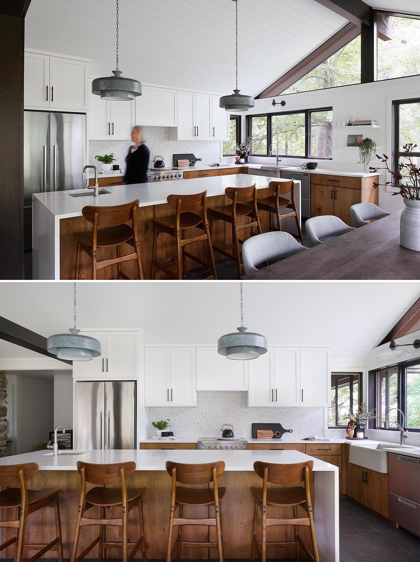 A modern kitchen with a large kitchen island provides ample countertop space, while the upper cabinets have a simple shaker style with black hardware, and the lower cabinets are wood.