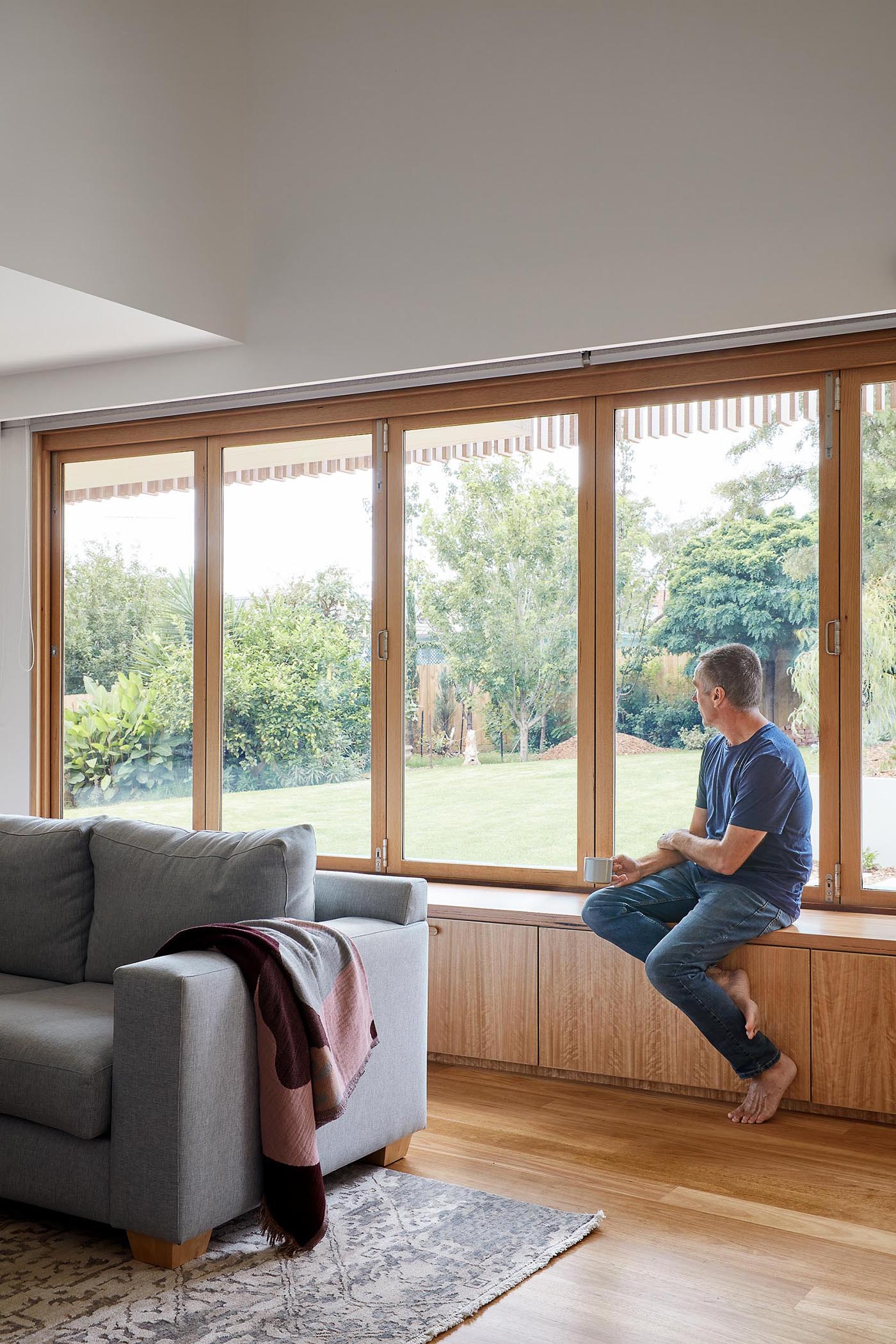 A modern living room has a bench below a series of windows that open to connect the interior with the bench on the other side of the windows.