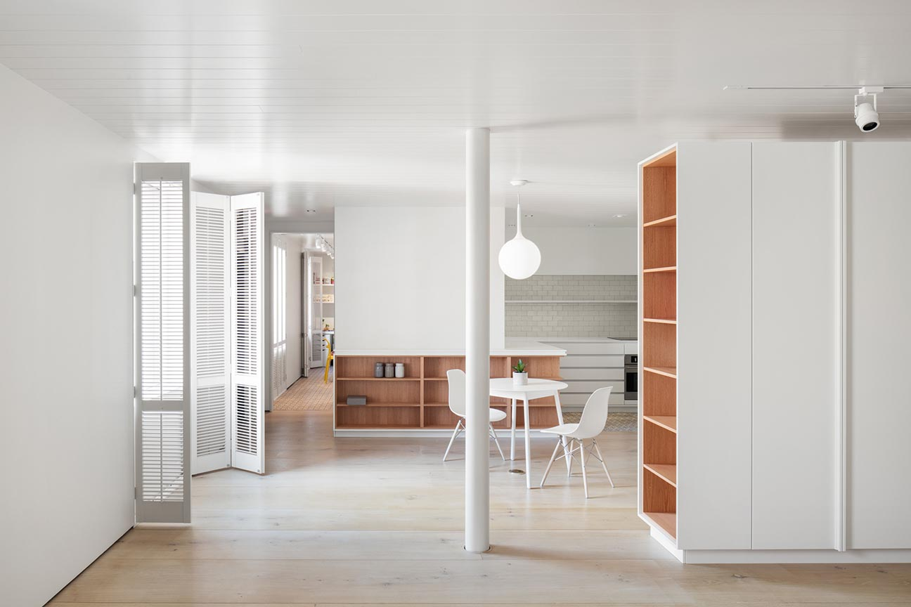 A modern office with wood lined shelves.