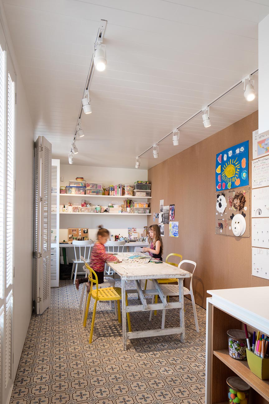 A modern playroom with shelving for storing craft items, and tables for creating.