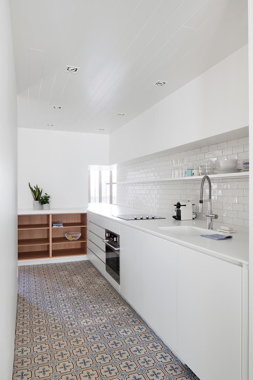 A modern and mostly white kitchen has wood shelf accents and colorful patterned tiles.