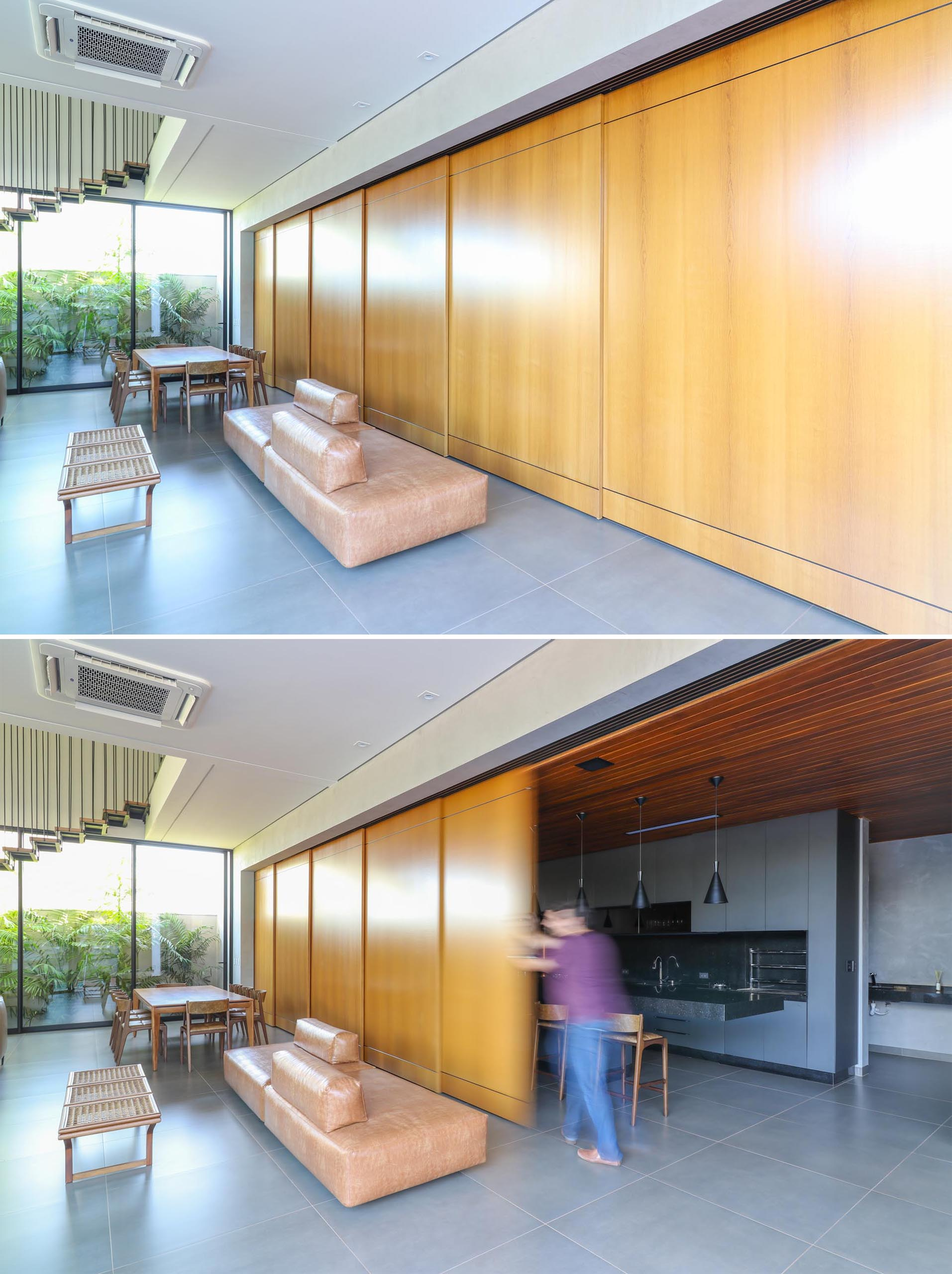 A modern home with a sliding wood wall that can hide the kitchen from the open plan dining area and living room.