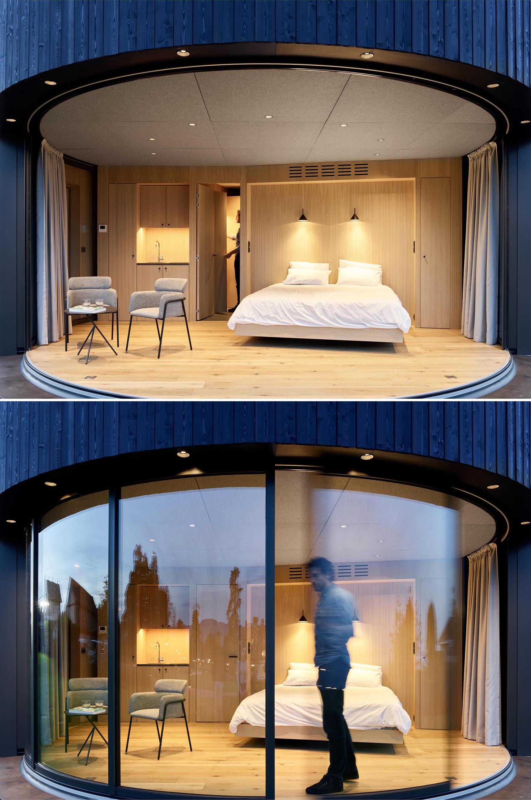 A modern round cabin with a curved glass wall that disappears.