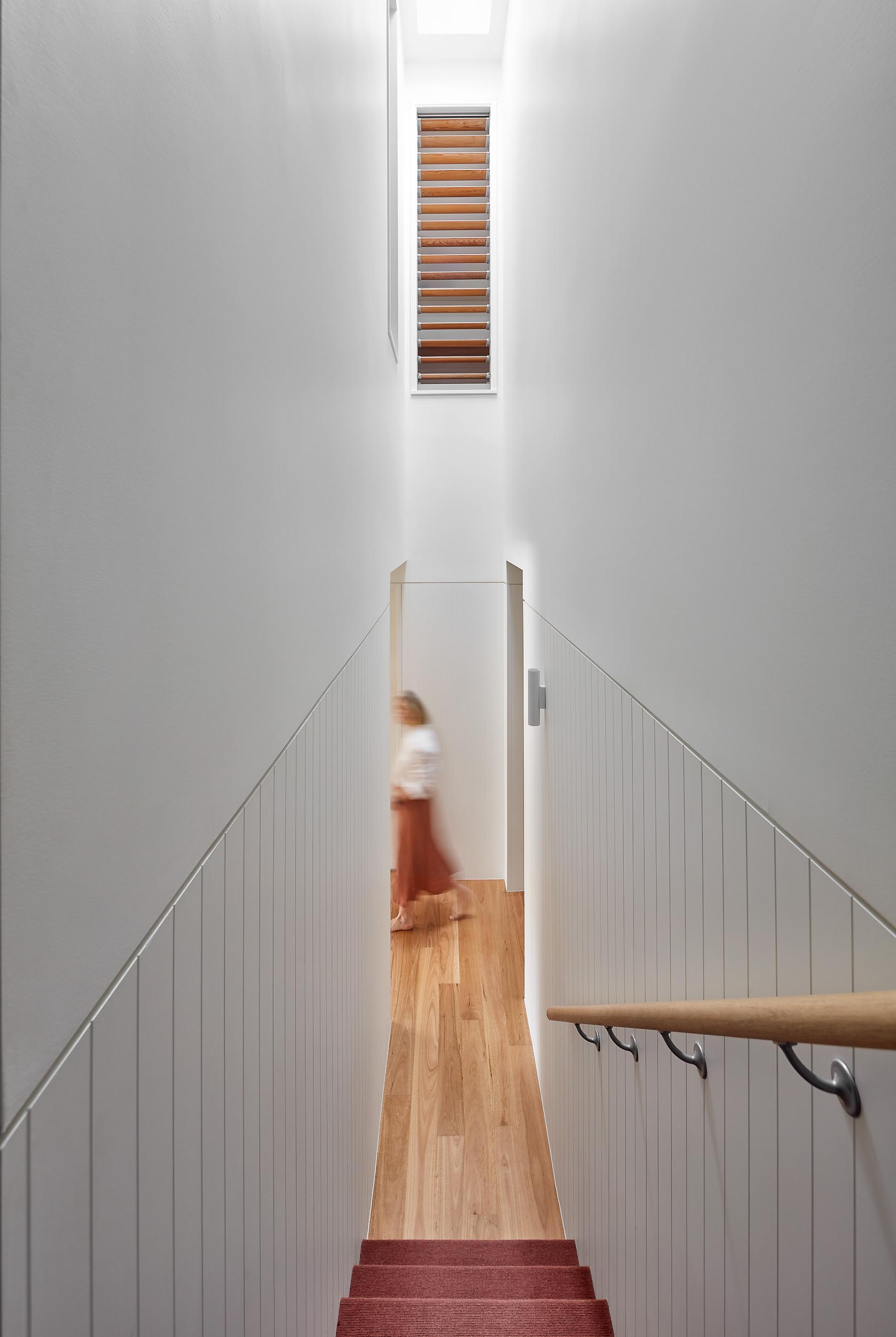 A staircase with a skylight connects the various floors of this renovated home.