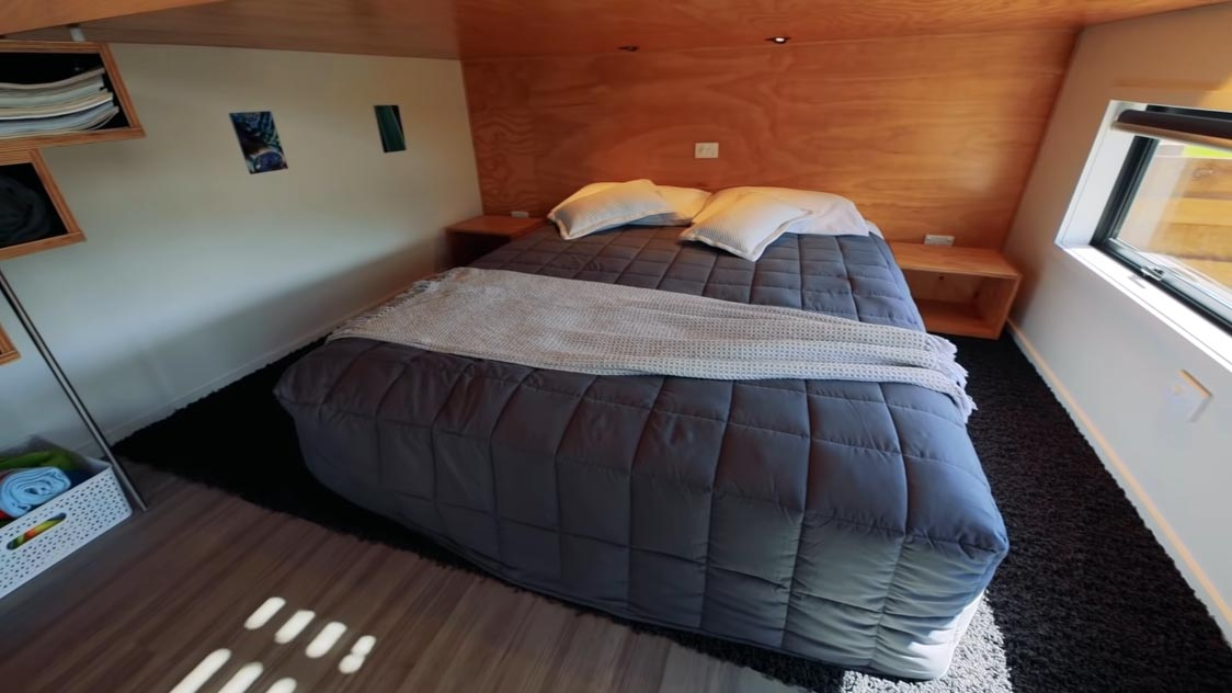 A modern tiny home with an open bedroom that includes a roll-out bed that makes it easier to change the bedding.