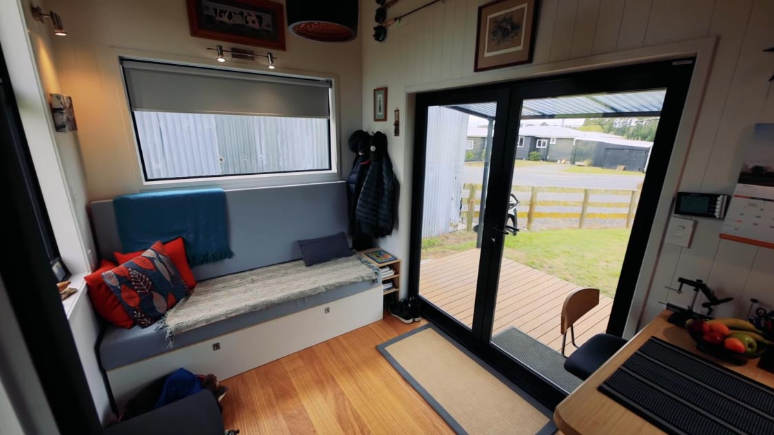 Stepping inside this modern tiny home, you're immediately met with the living room that includes a sofa that provides hidden storage as well as transforms into a bed for when guests visit.