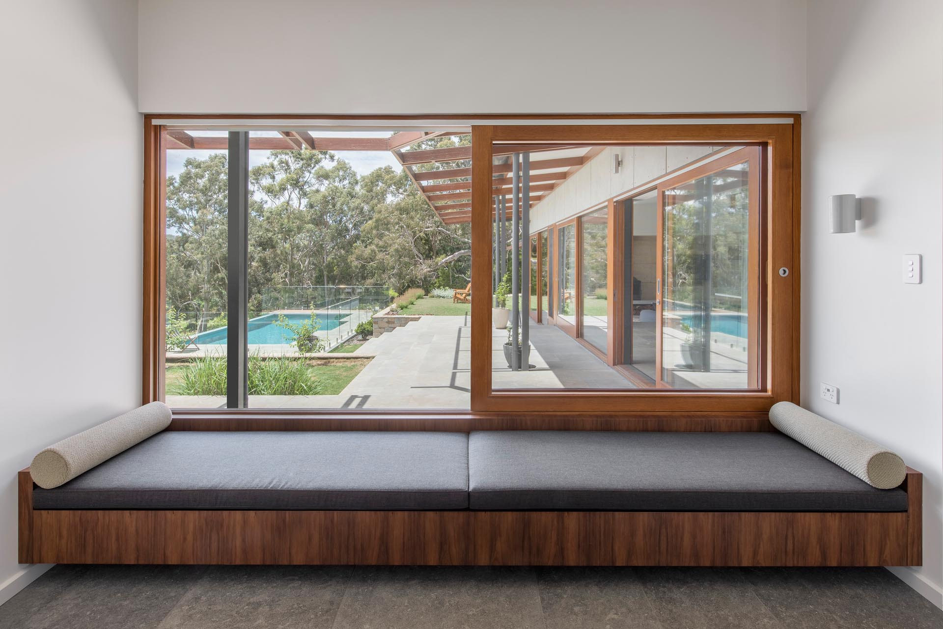 A quieter space in thsi home that also opens to the outdoors, is a full width day bed by the window, that takes advantage of the terrace and pool views.