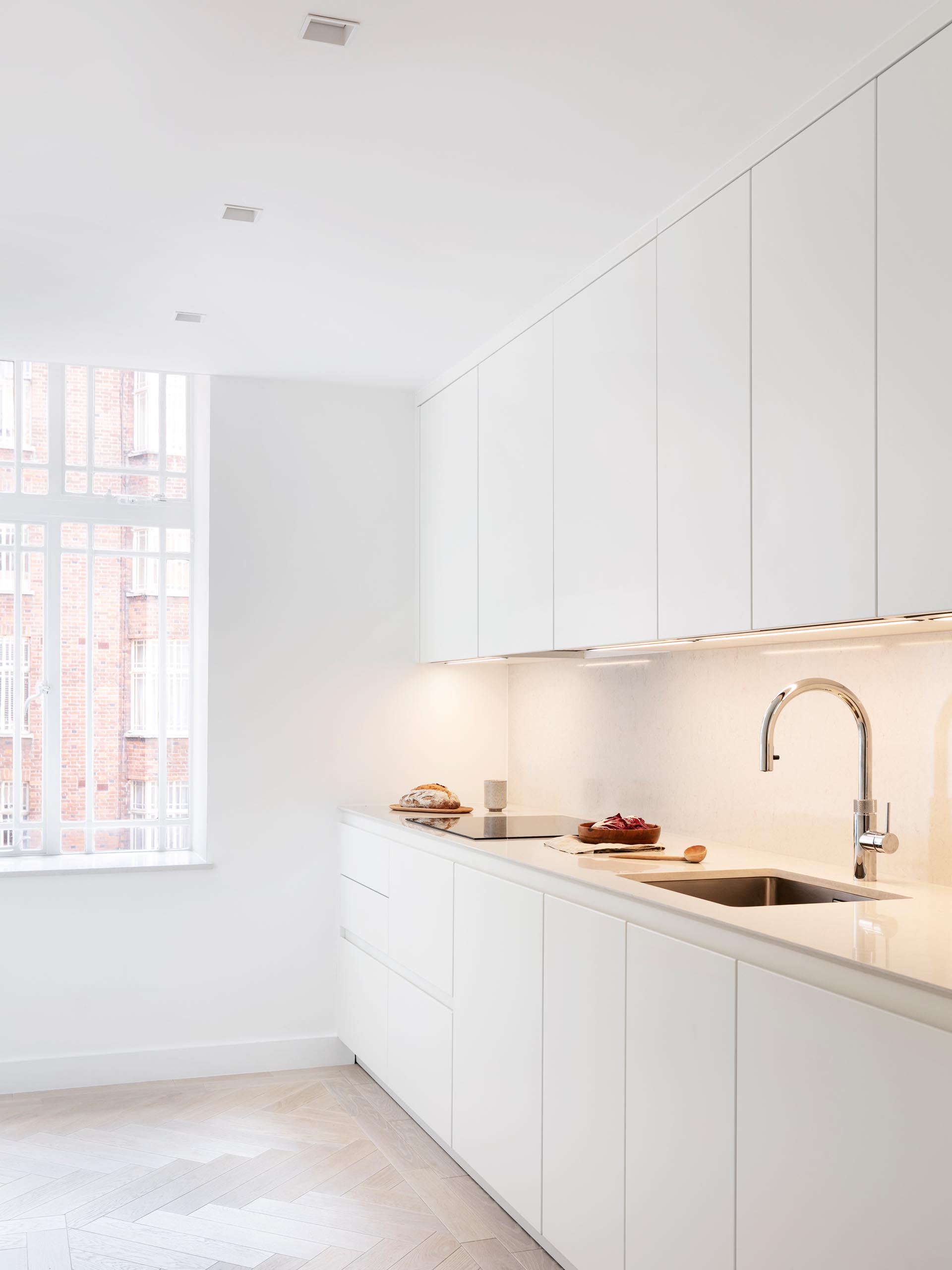 In this modern kitchen, lighting has been installed underneath the minimalist white cabinets, lighting the backsplash and countertop.