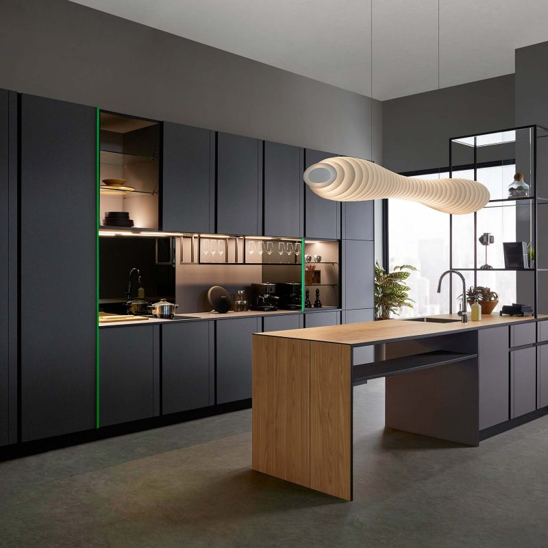 Timeless kitchen opens up to more eating, prepping, cooking and entertaining space than imaginable, with the kitchen island in the foreground while showcasing a clean, modern wall of cabinetry with a minimalistic pantry, enclosed storage and open shelving in the background.