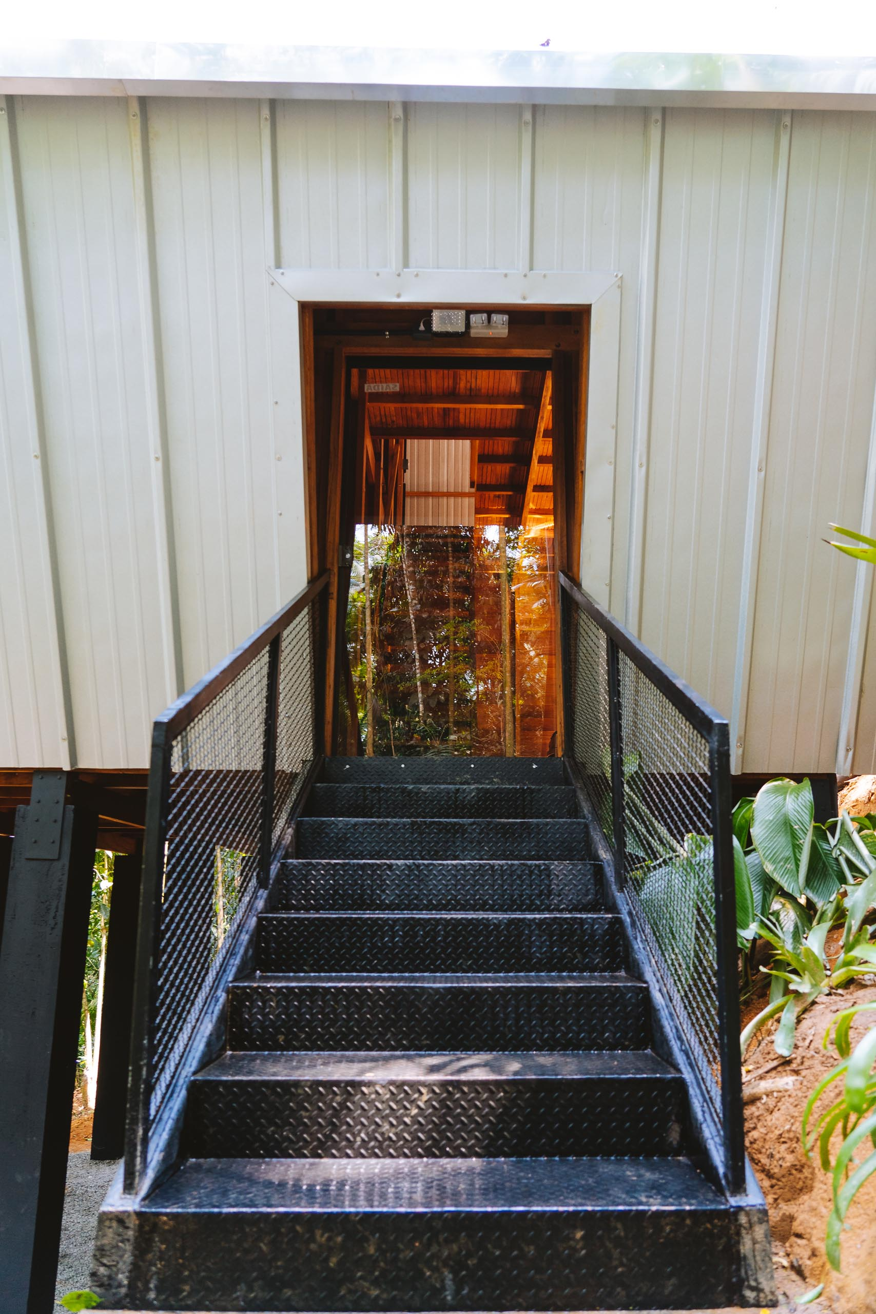 Black metal stairs and handrails provide entry to a raised A-frame cabin.