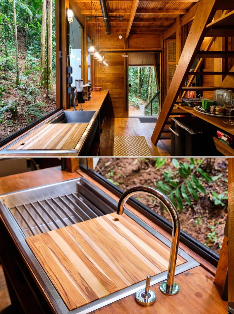 The kitchen of an A-frame cabin with a warm wood interior, includes open shelving and large windows.