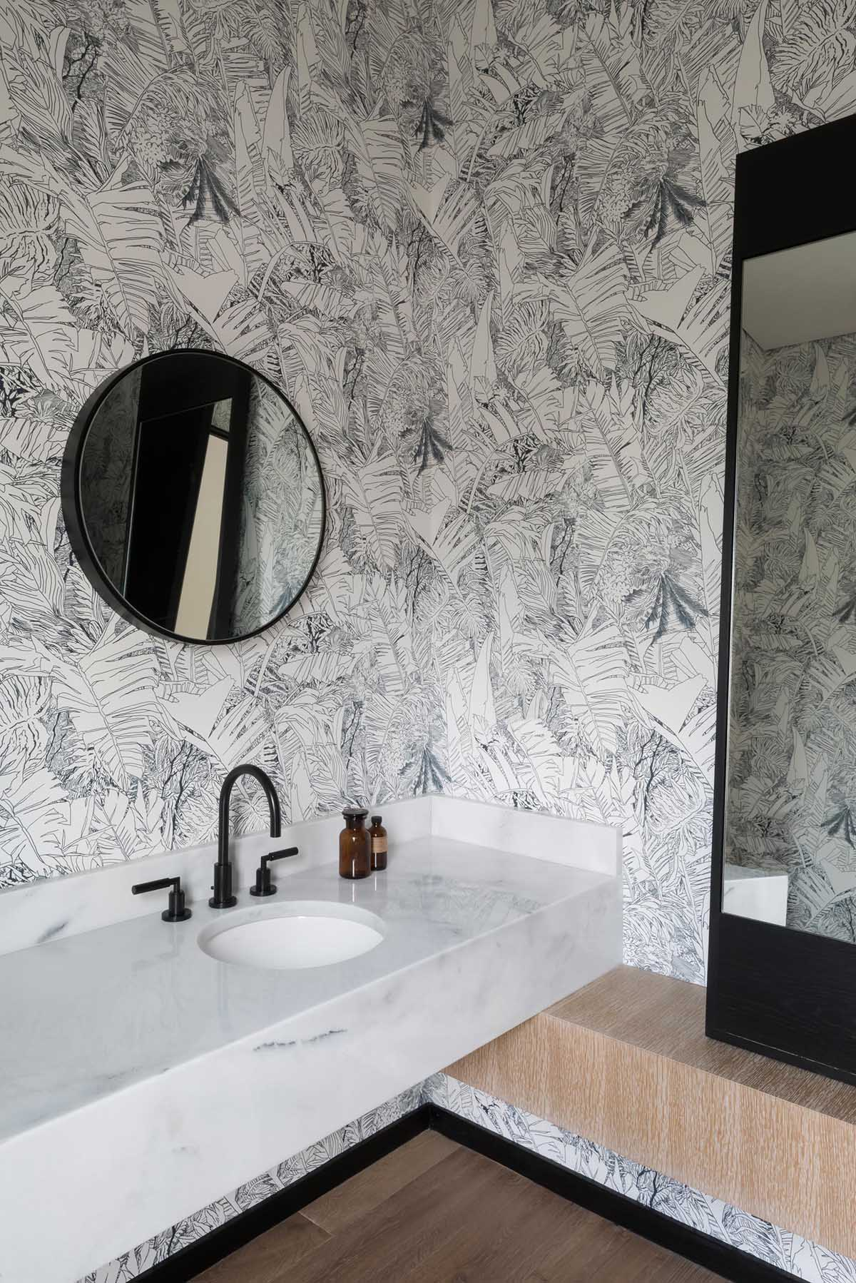 A modern bathroom with black and white tropical print wallpaper.