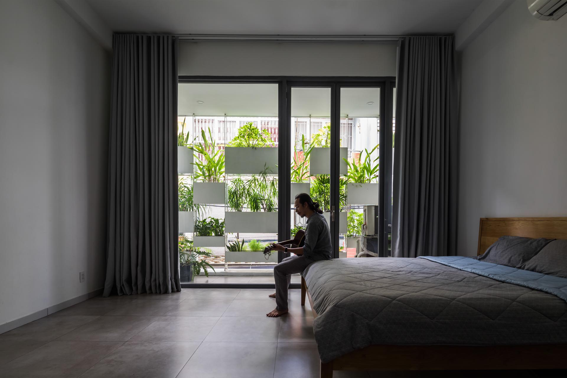 A minimalist bedroom with a view of built-in planters.