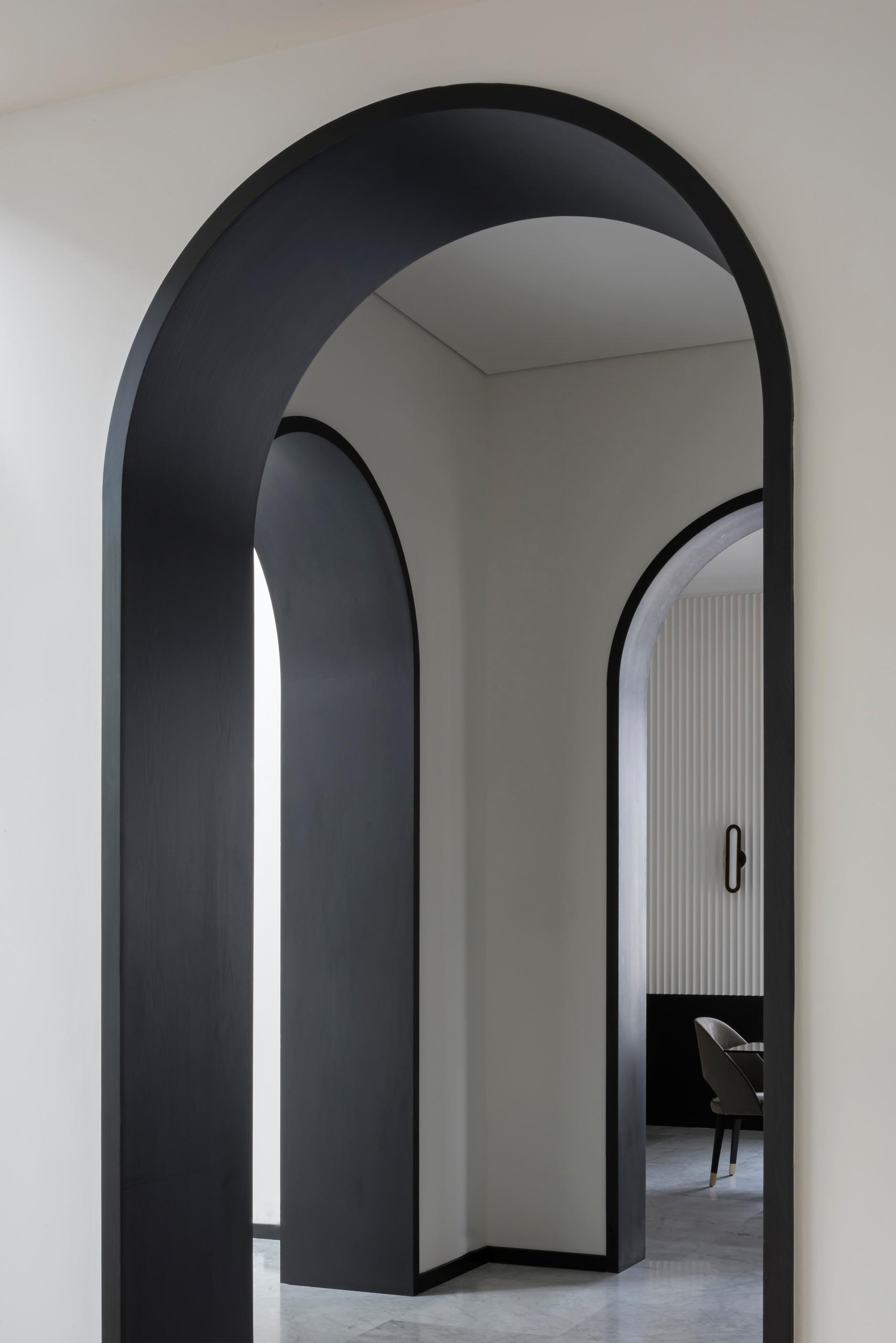The black lined arches meet with the trim at the bottom of the walls, which wraps around the rooms, as well as the black window frames and stairs structure.
