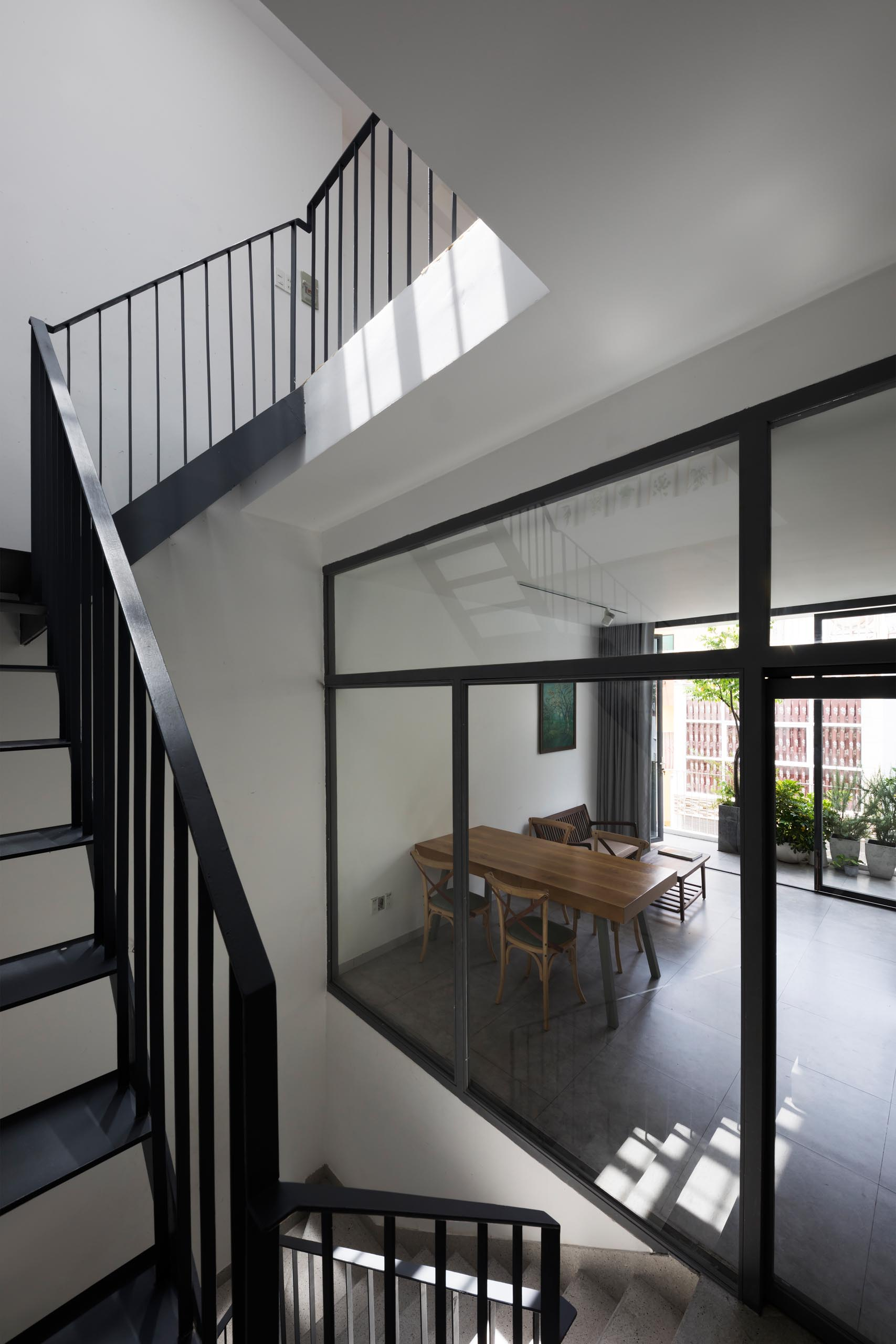 A modern home with black steel stairs and glass walls.