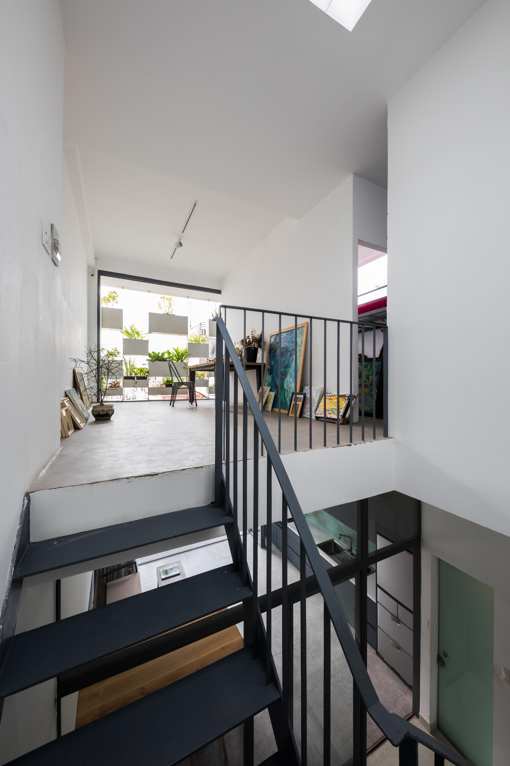 At the top of stairs in this modern home, there's an art studio with simple white walls and space for creating.