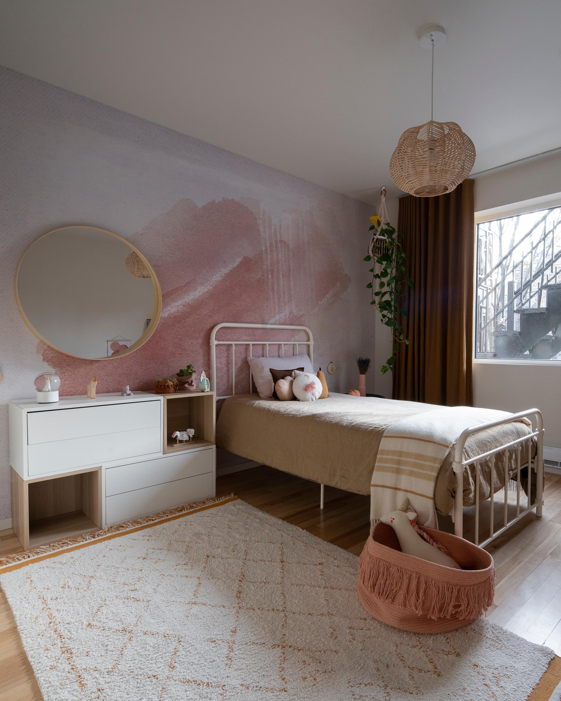 A modern kid's bedroom with a blush-pink and natural palette, and a watercolor wall mural.