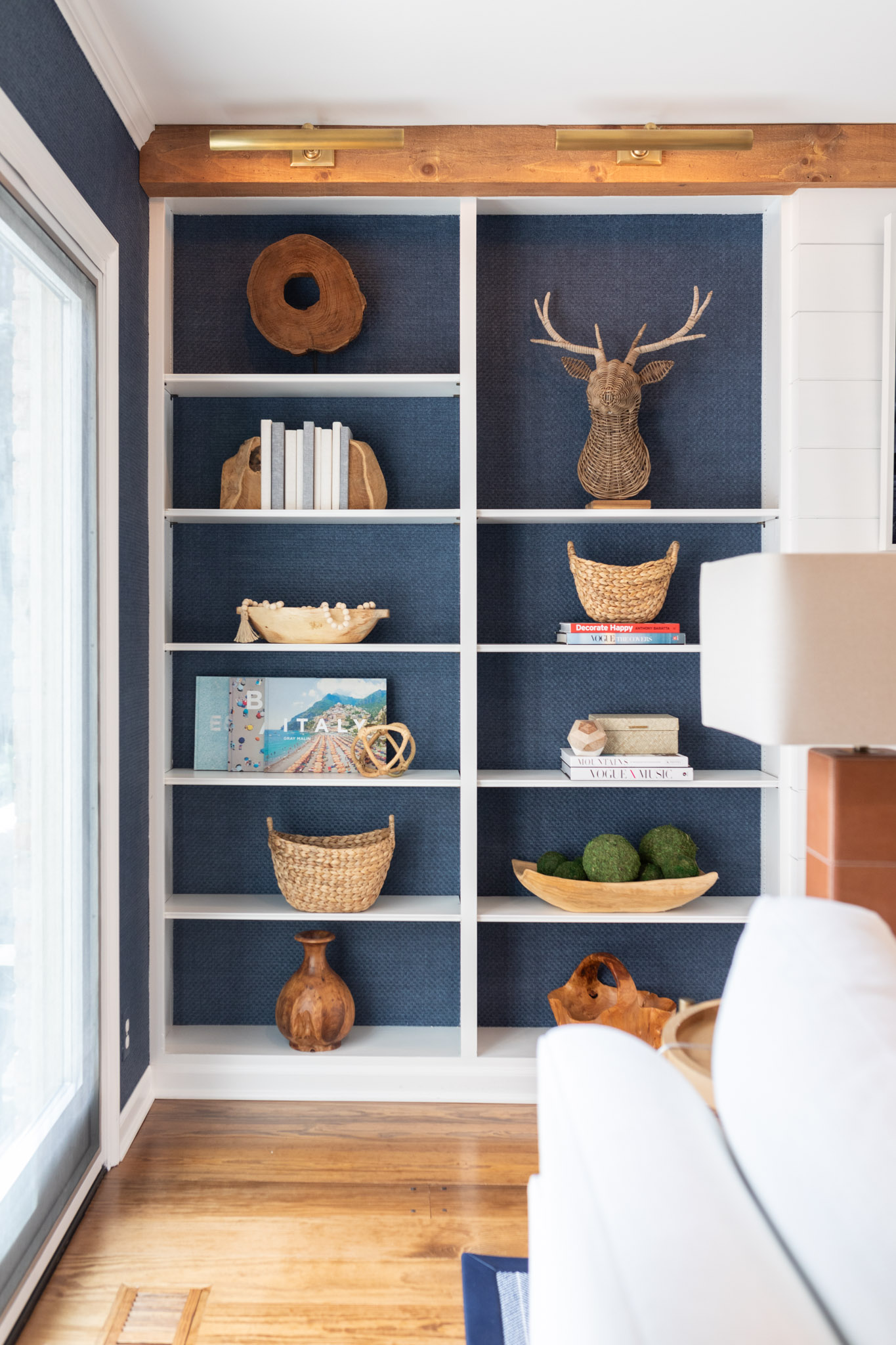 To incorporate texture, the designers of this living room added a blue grass, cloth wallpaper to the walls, that also lines the back of the shelving that are located on either side of the fireplace.