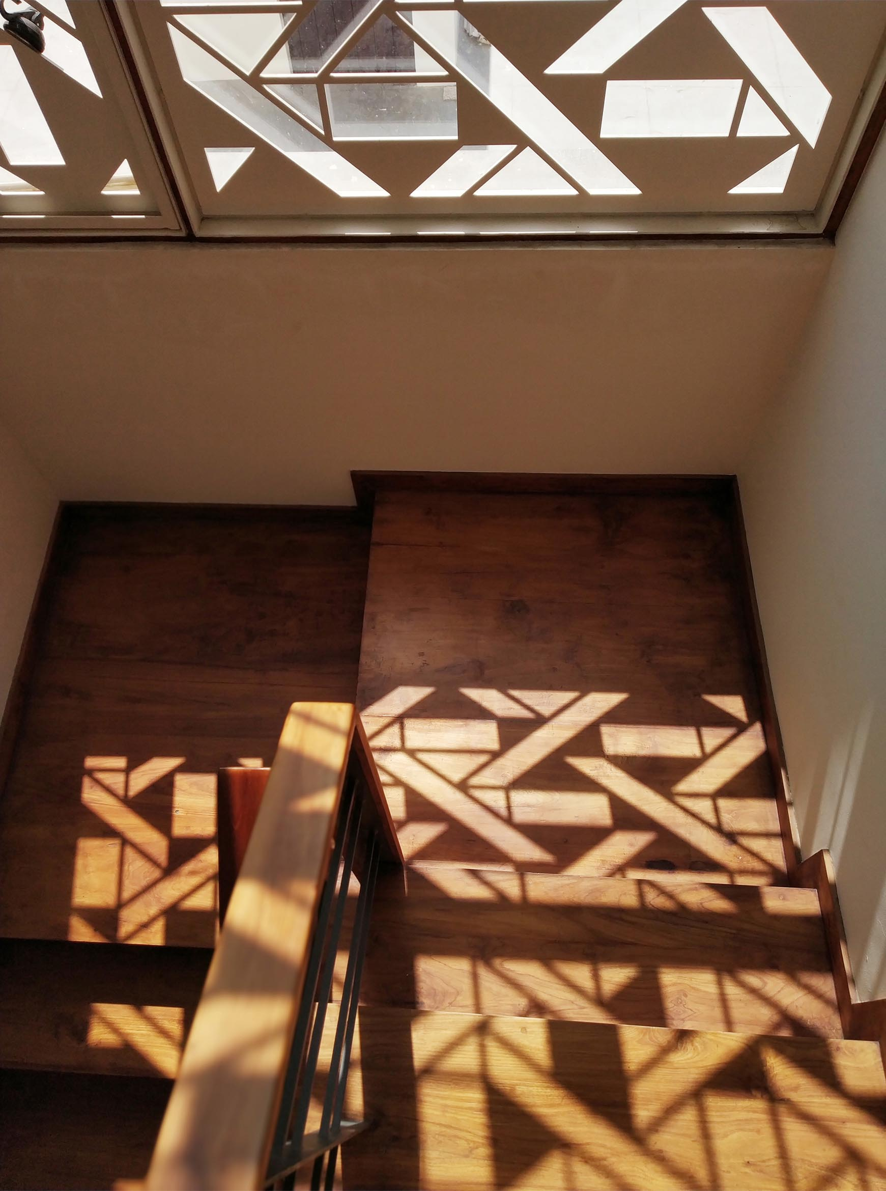 A white window screen with a geometric design casts interesting shadows on the walls and floor.