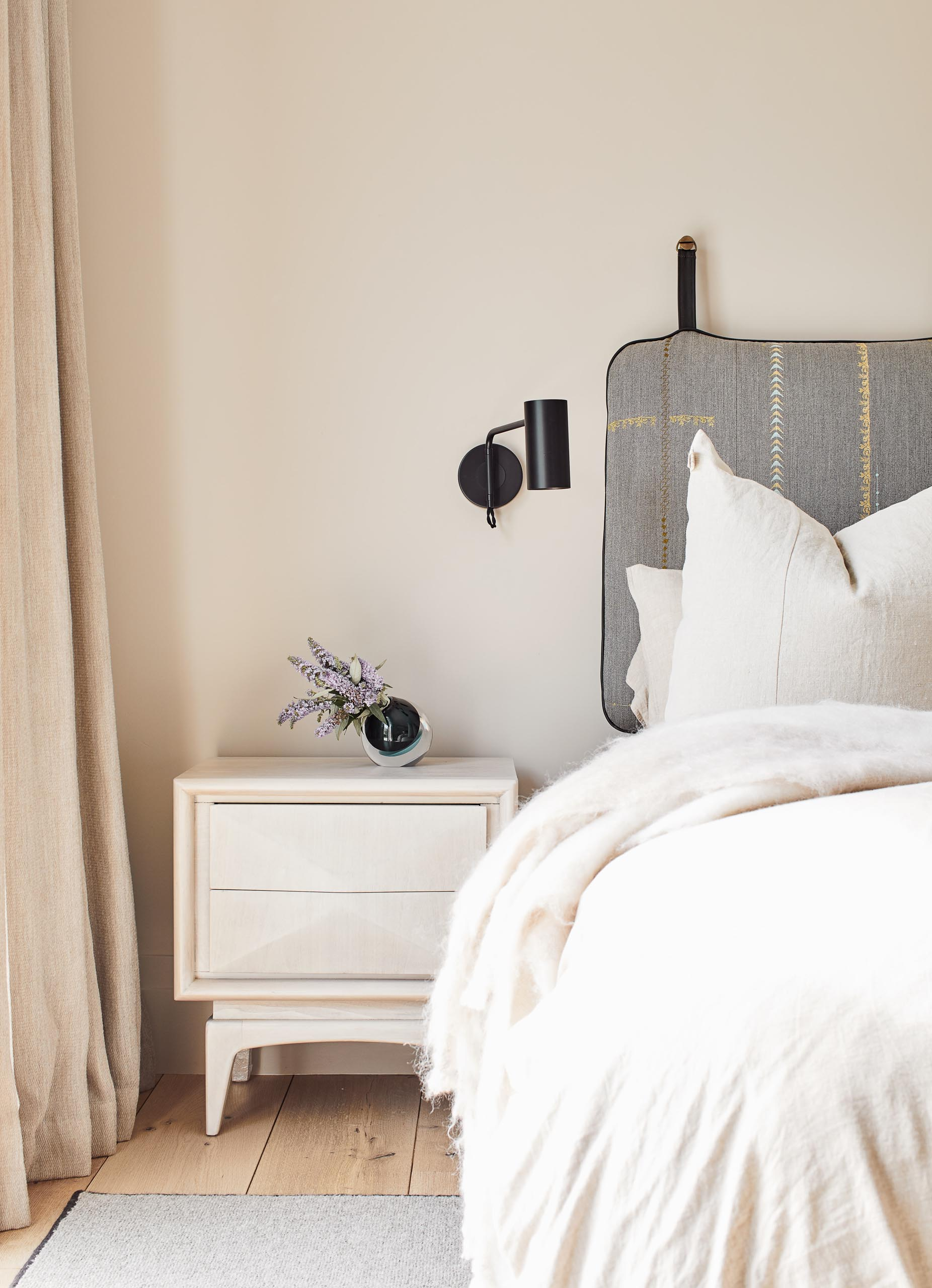 In this guest bedroom, the upholstered headboard hangs from the wall, while minimalist black sconces are positioned above bedside tables.