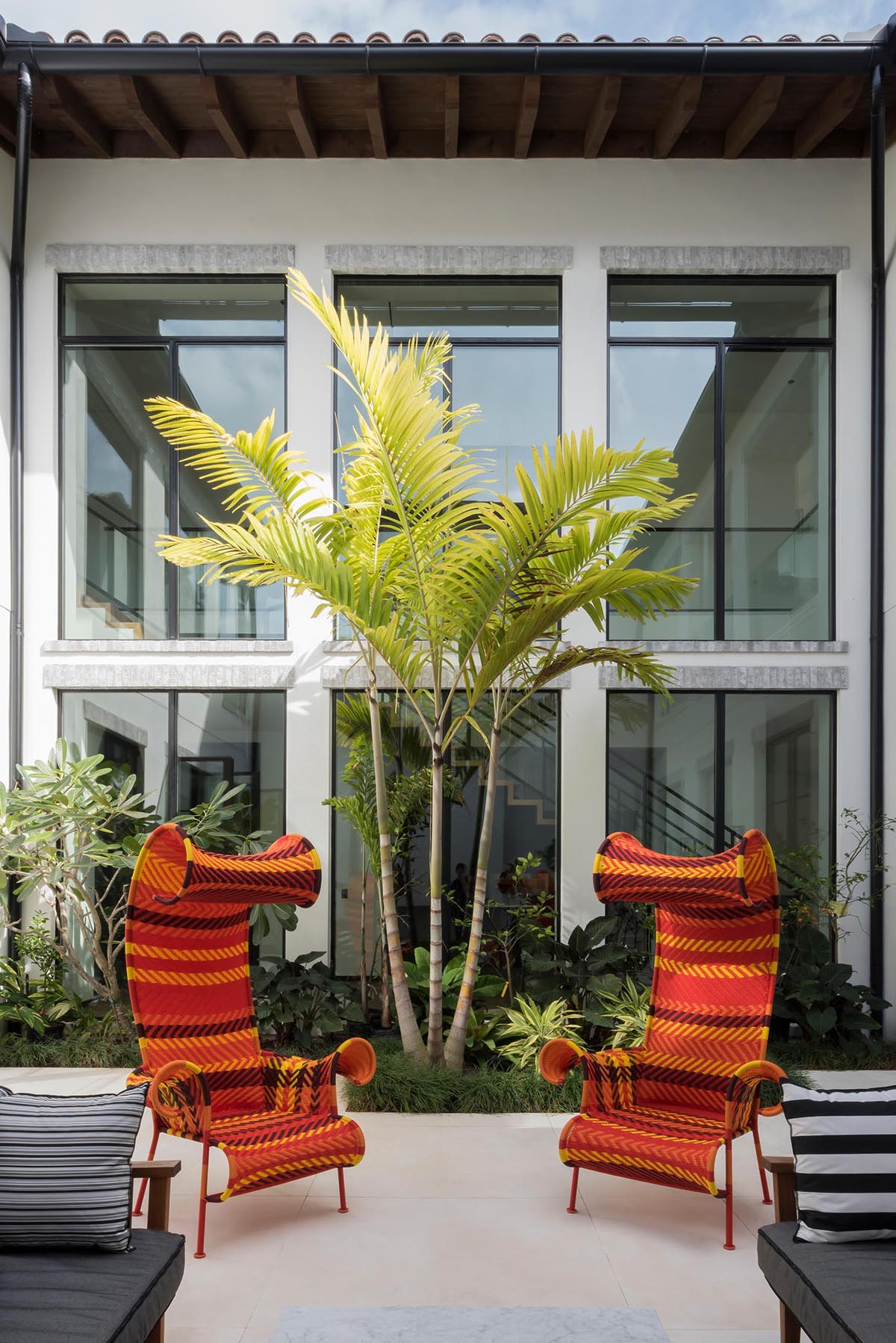 An internal courtyard has a tiled patio with lounges and sculptural chairs, while a garden alongside one wall adds greenery.