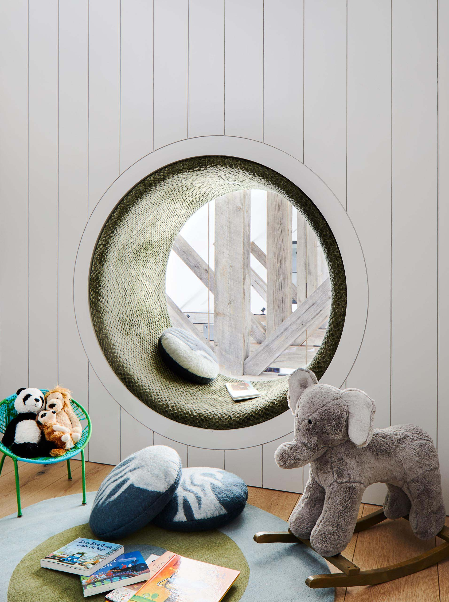 In this modern kids room, there's a cozy round window seat with an upholstered cushion that lines the space.