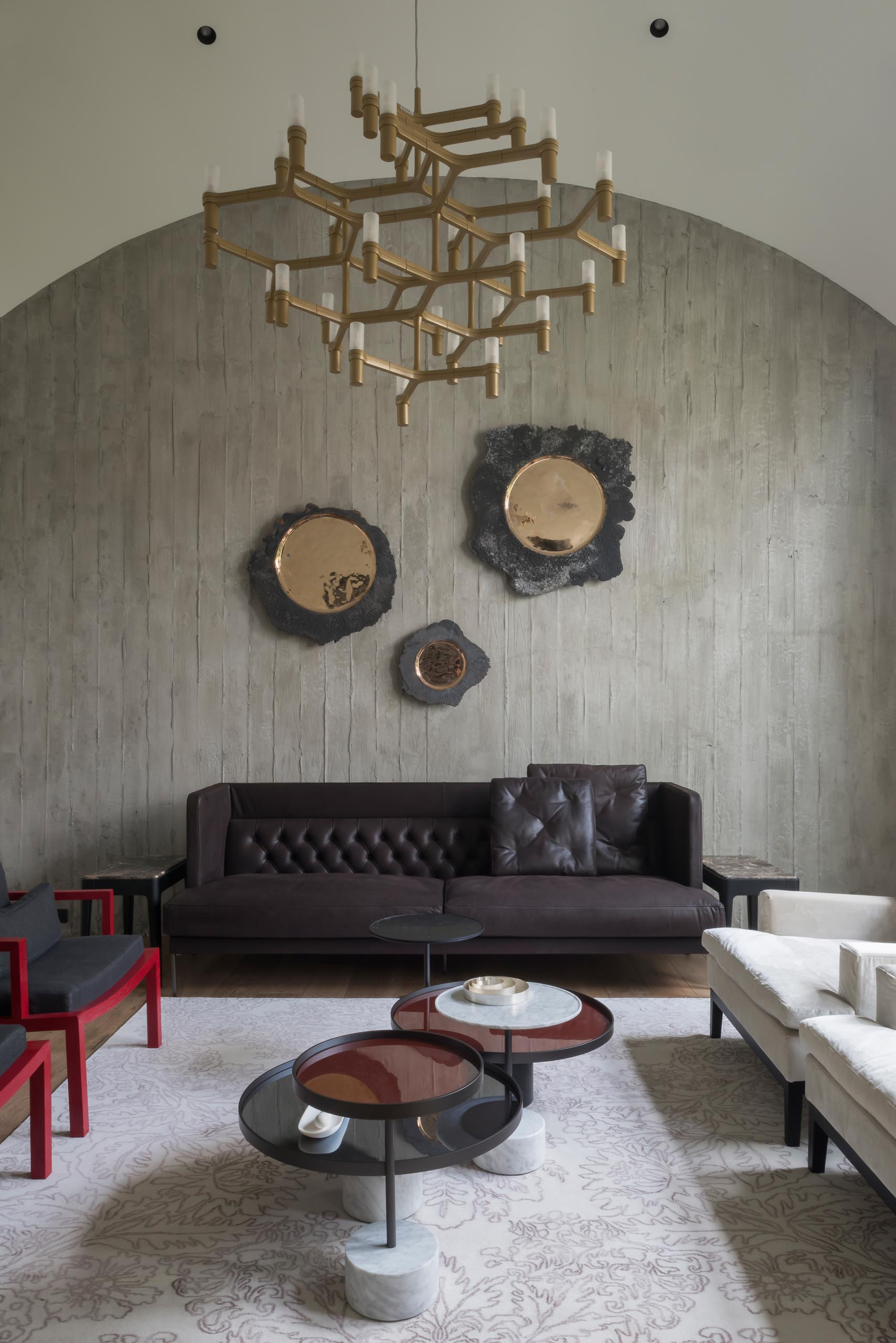 The living room has a curved ceiling, exposed concrete wall, and hardwood floors.