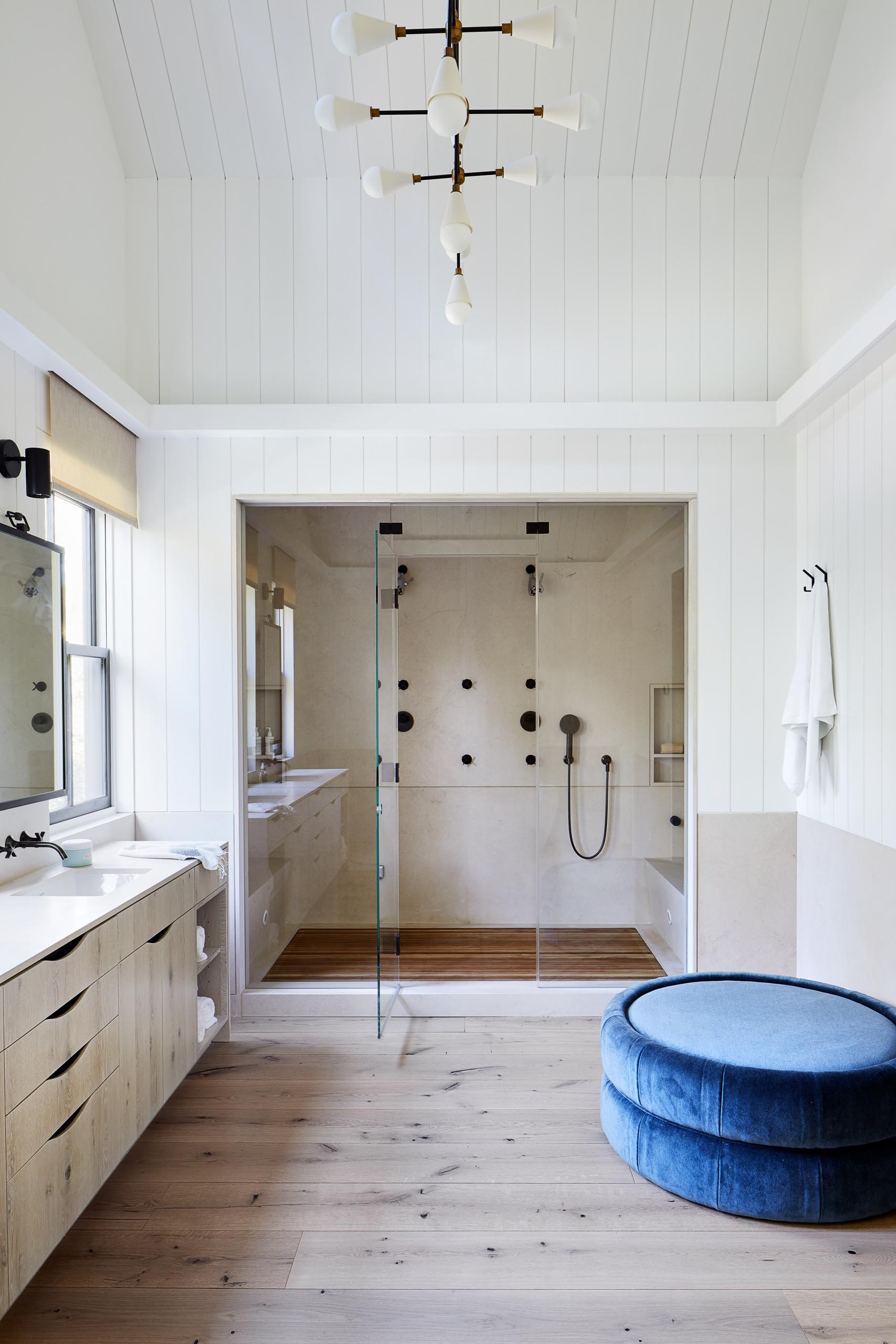 This master bathroom includes a long double sink vanity with the mirrors perfectly positioned between the black framed windows. Adjacent to the vanity is a walk-in shower with benches and double shower heads.