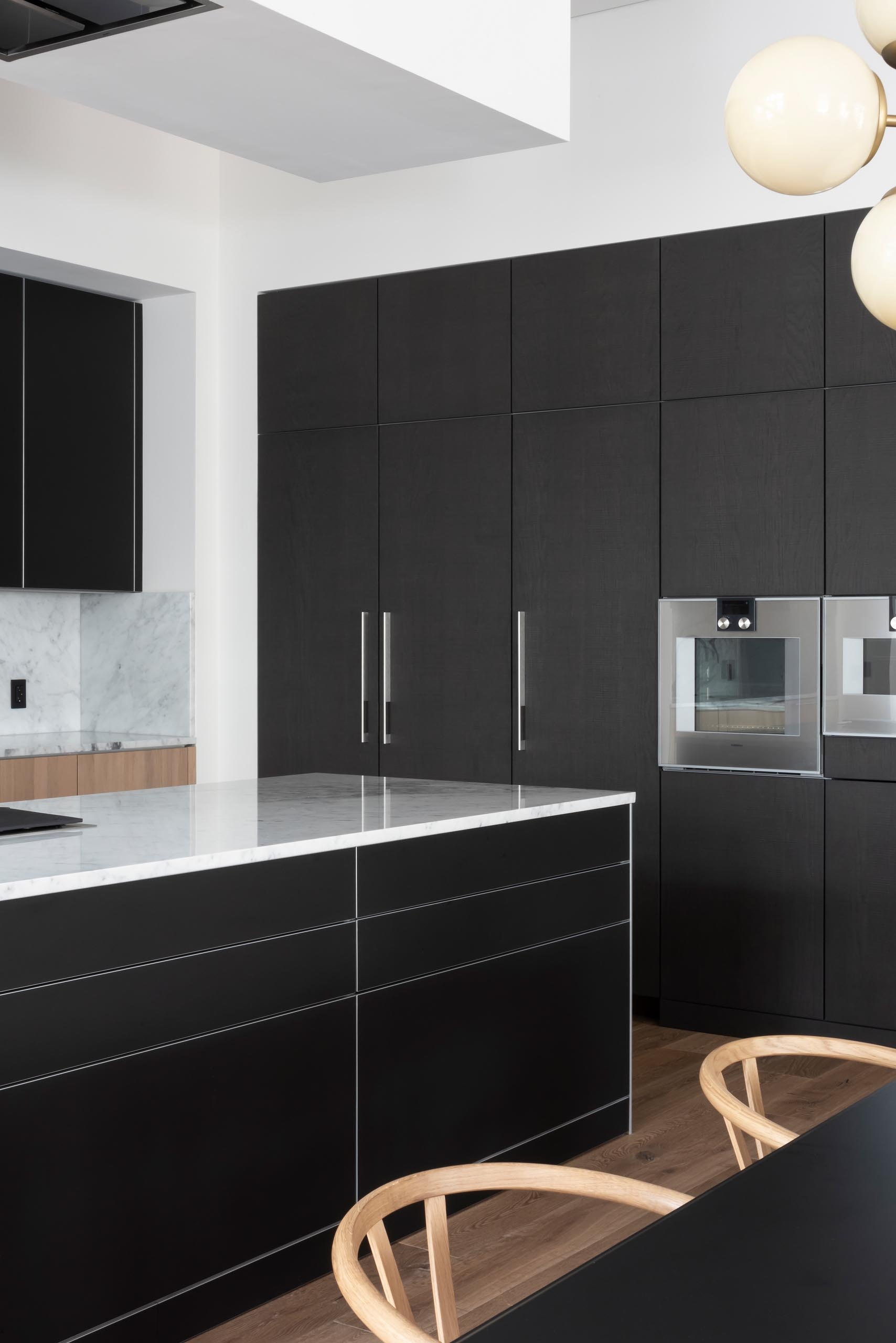 In this modern kitchen, matte black cabinets are complemented by gray marble countertops and backsplash.