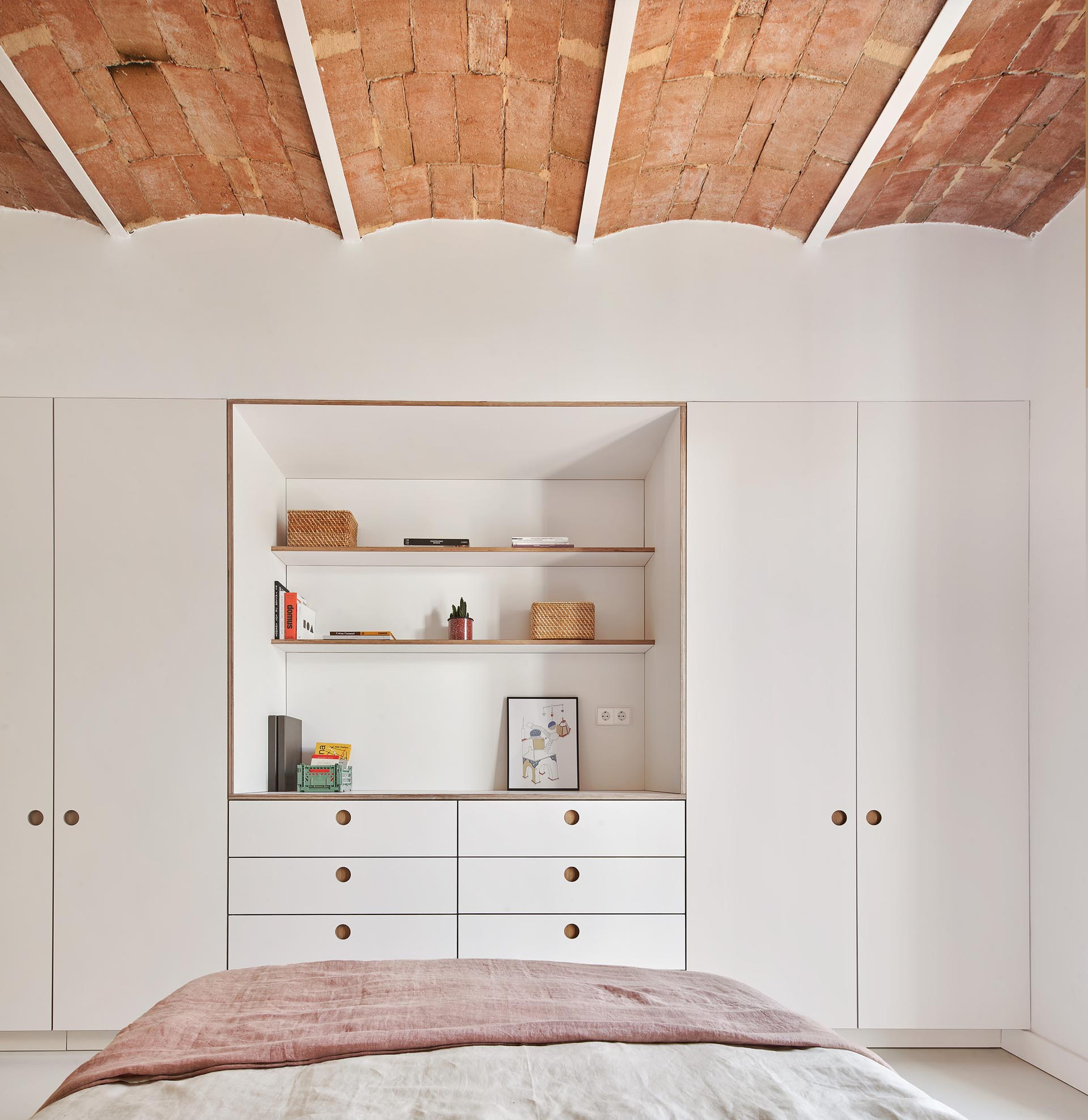 Minimalist bedroom closets and drawers with recessed finger pulls.