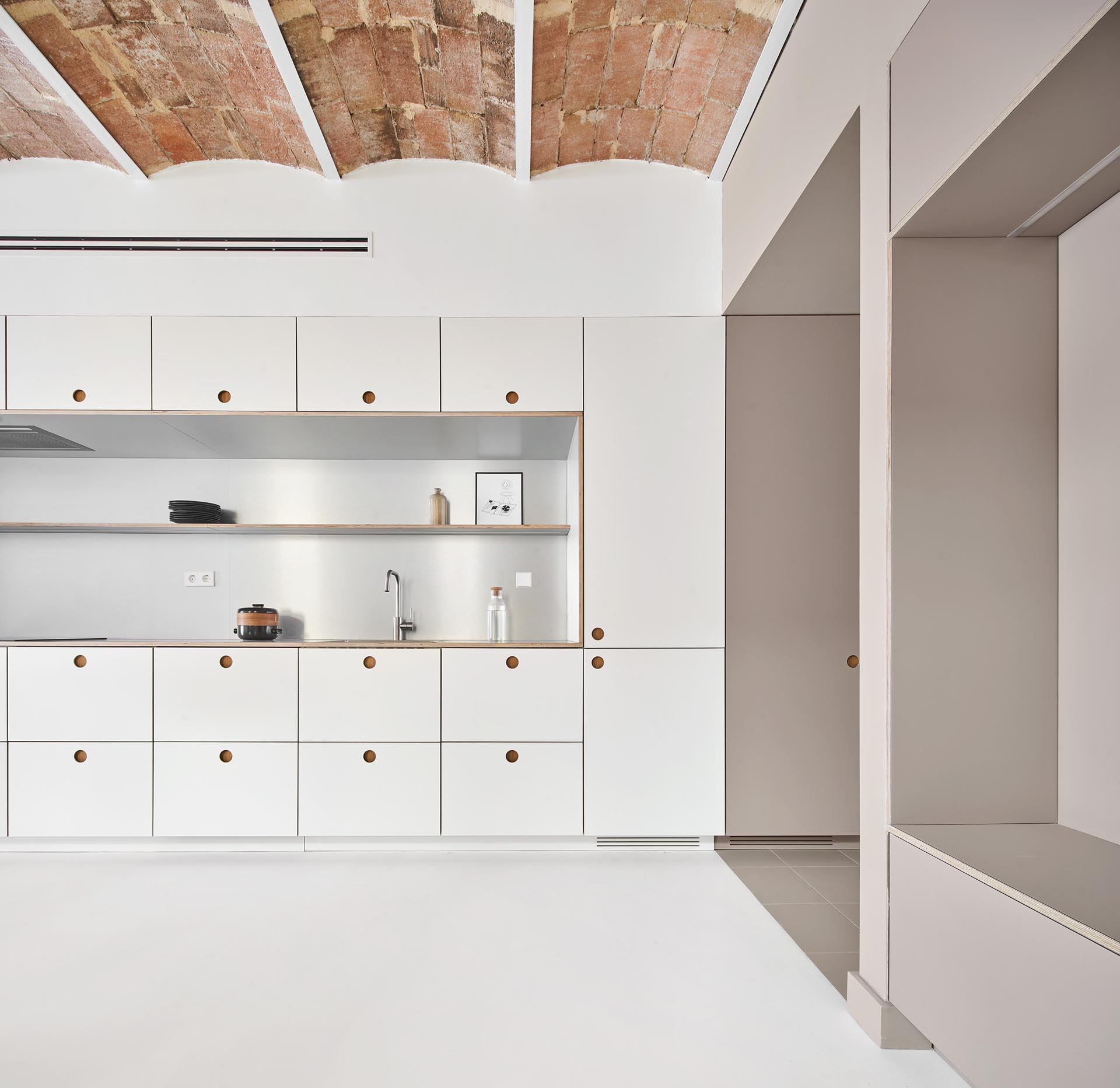 Minimalist kitchen cabinets and drawers with recessed finger pulls.