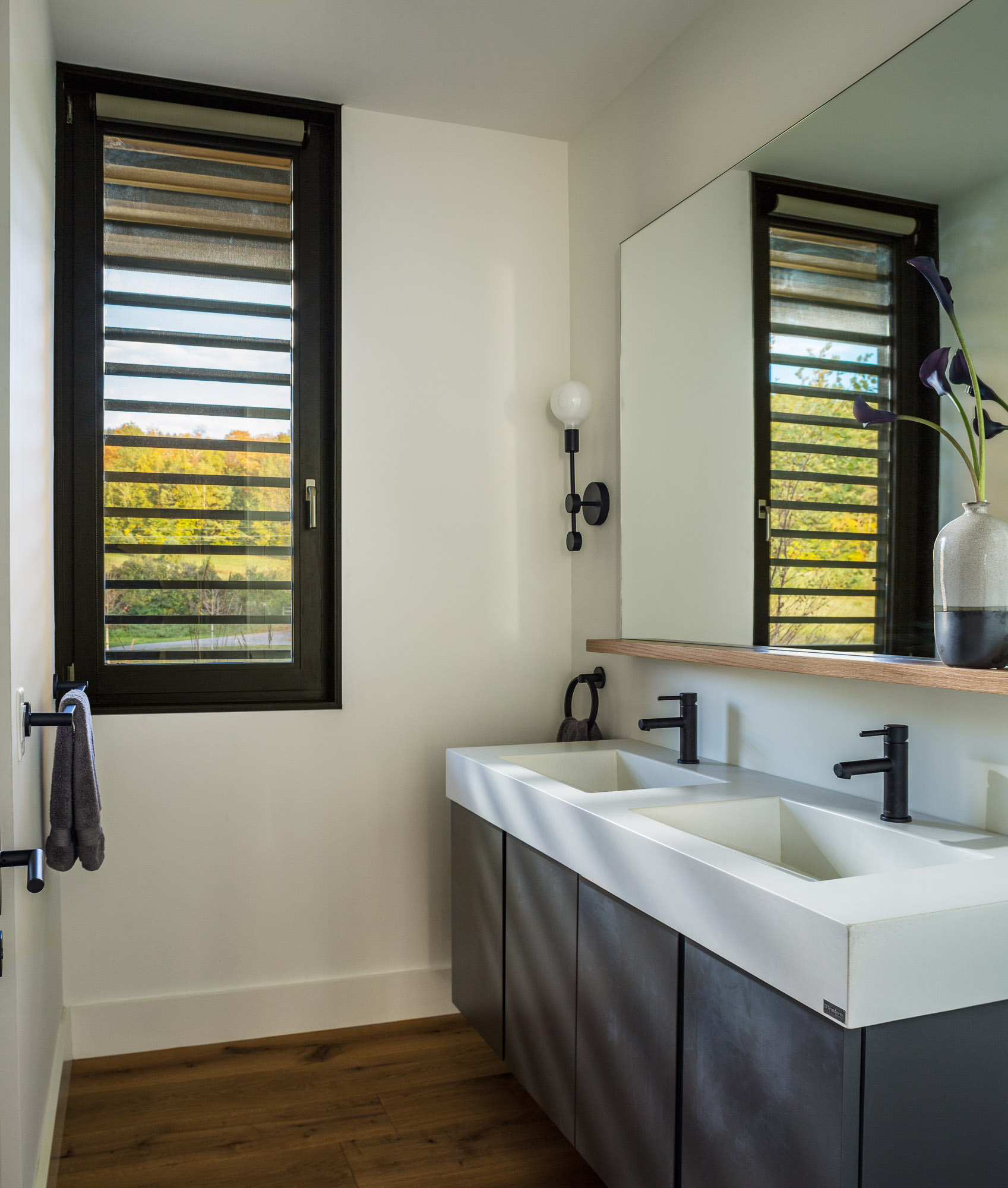A modern bathroom with a double vanity and a large mirror, matte black light fixtures, and a louver window.