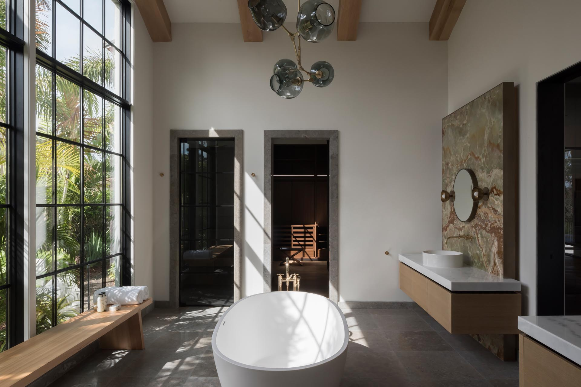 In this modern bathroom, tall windows flood the interior with natural light, while a freestanding bathtub takes center stage.