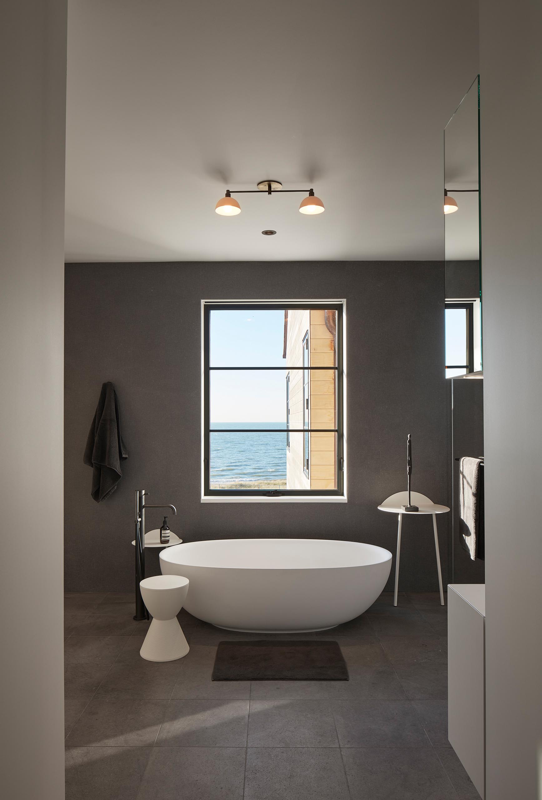 In this modern master bathroom, a freestanding bathtub has been positioned below the window, while dark gray walls complement the gray tiles on the floor.